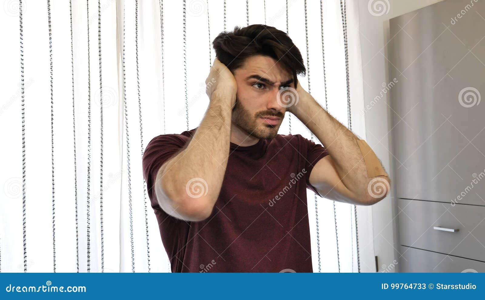 Hombre joven que cubre sus oídos, demasiado ruido