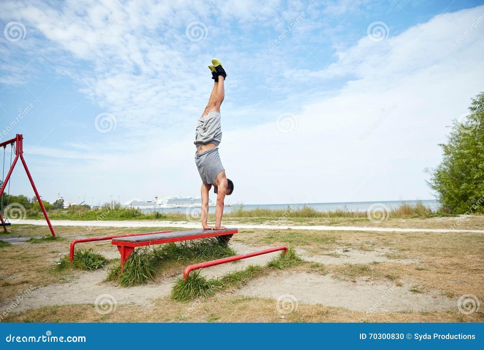 Hombre joven que ejercita en banco al aire libre foto de for Banco de paletas al aire libre