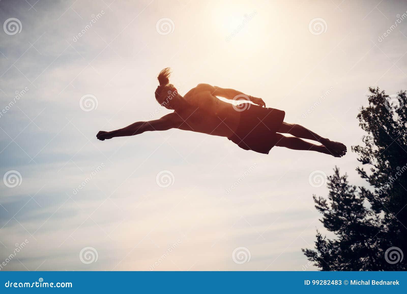 Hombre joven que eleva y mantiene flotando en el aire