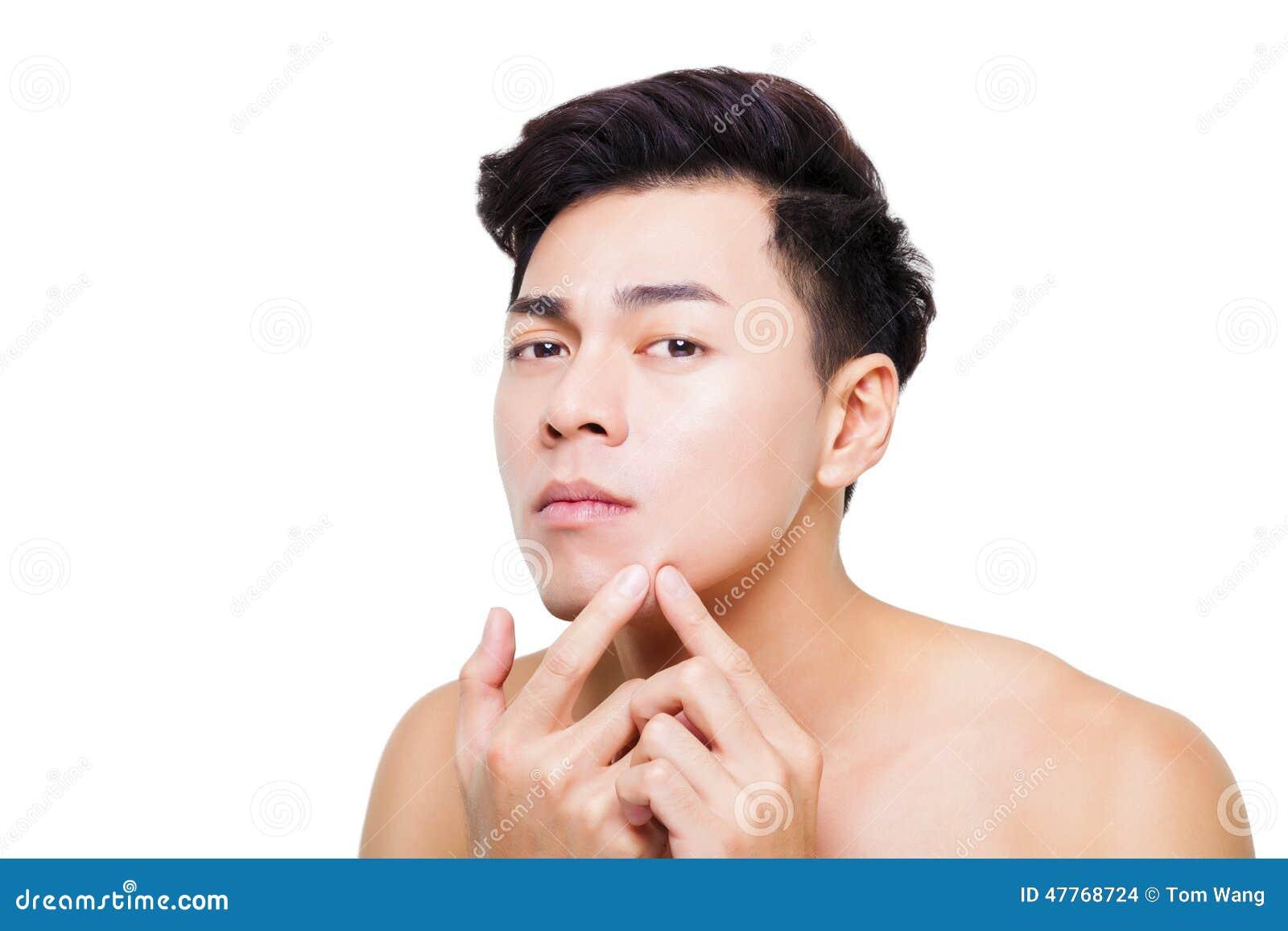 Hombre joven que exprime la espinilla