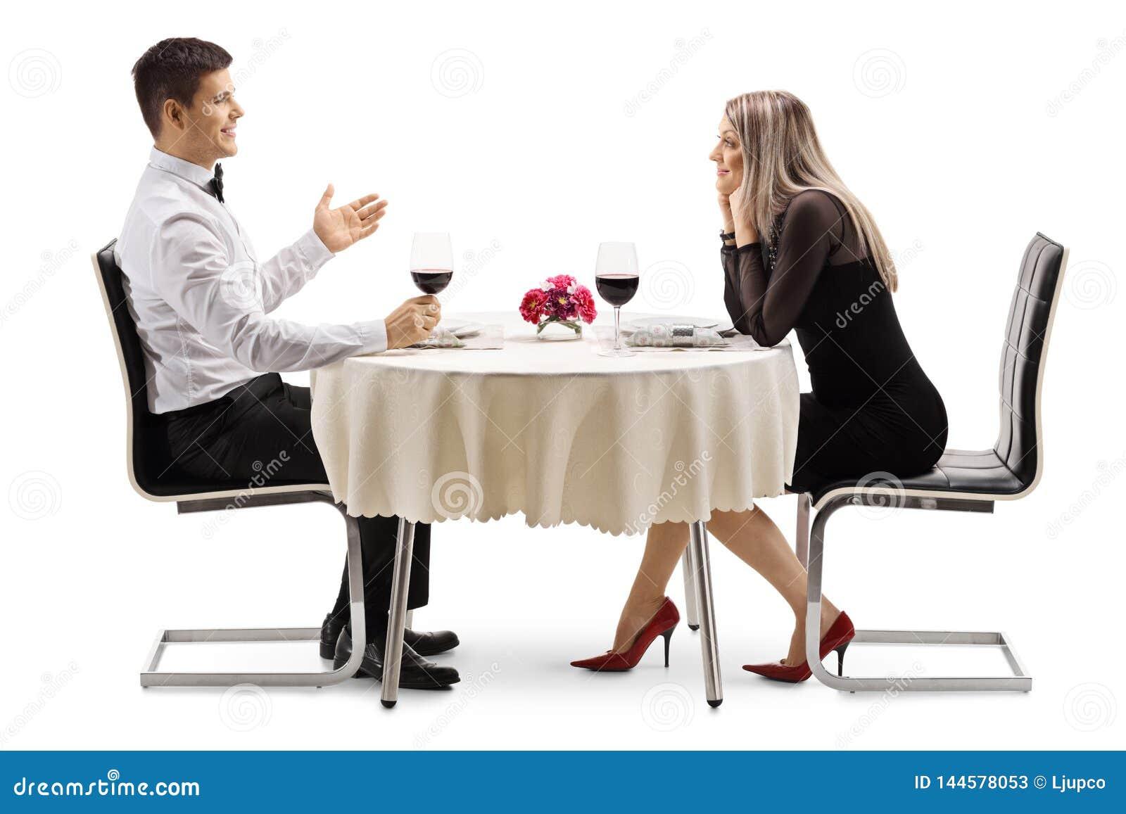 Hombre joven que habla con una mujer joven en una tabla del restaurante