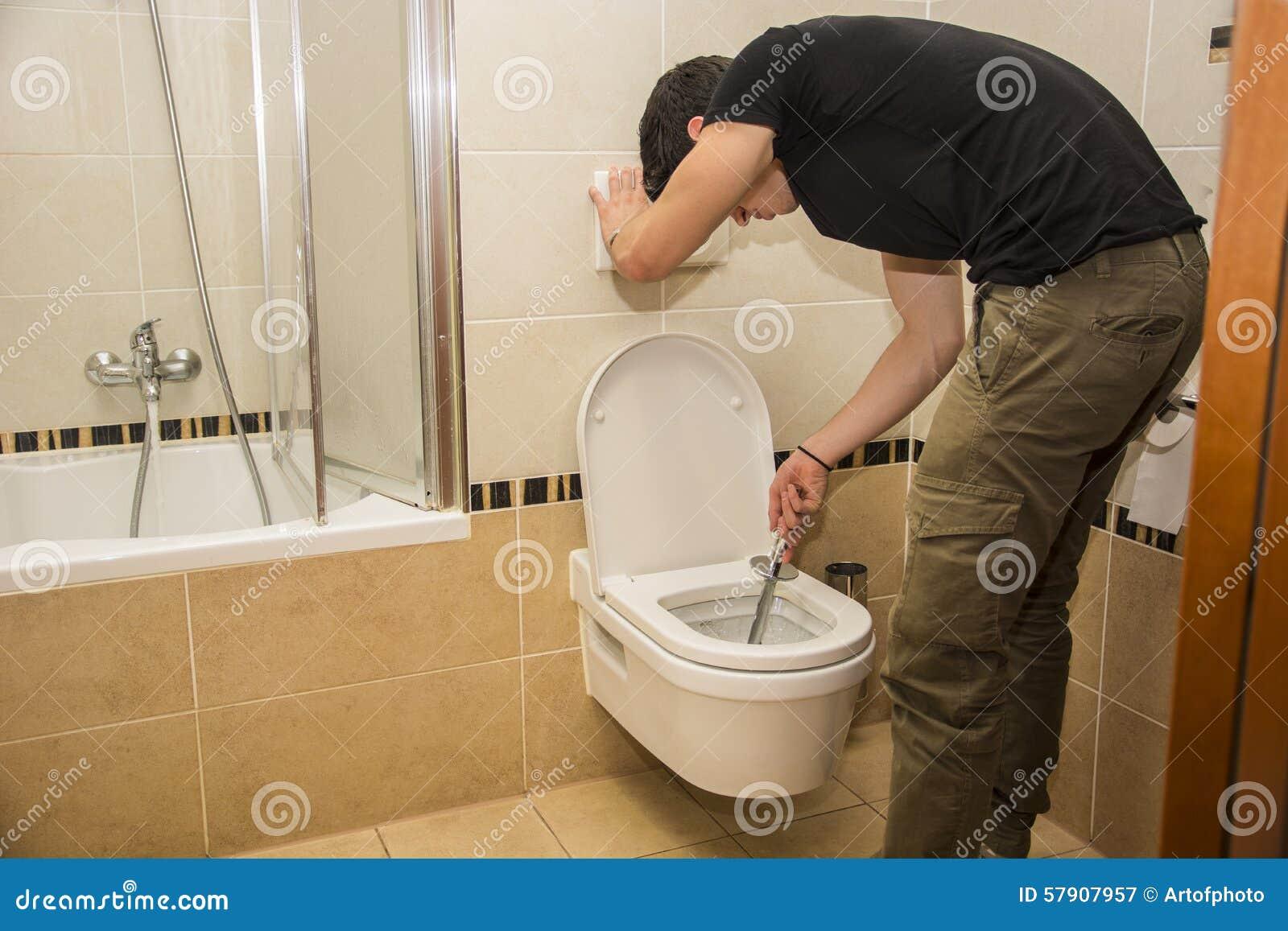 Hombre Joven Que Limpia El Servicio Del Cuarto De Baño, Limpiando ...