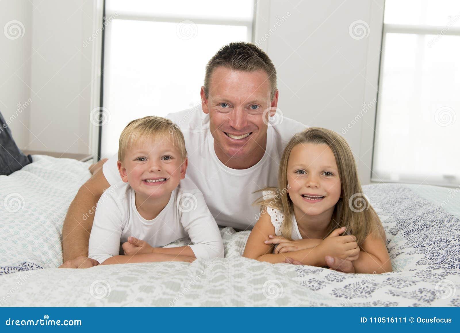 Hombre joven que miente en cama así como sus pequeños el jugar del hijo del dulce 3 y 7 años y de la hija feliz en los niños l de