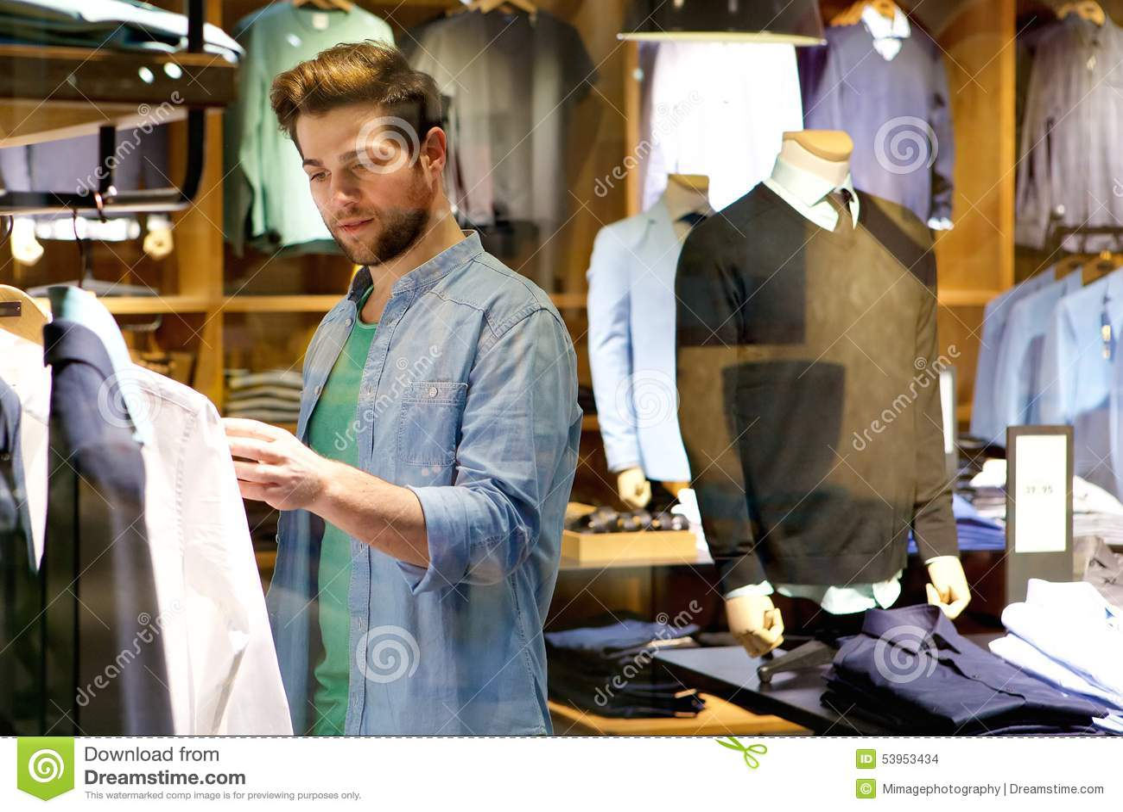 a4f91336e97a7 Hombre Joven Que Mira La Ropa Para Comprar En La Tienda Foto de ...