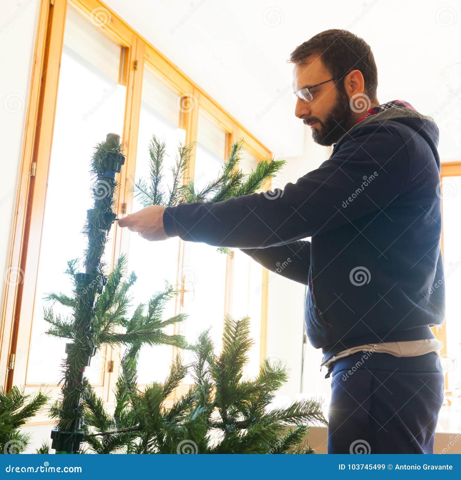 Hombre joven que monta el árbol de navidad artificial
