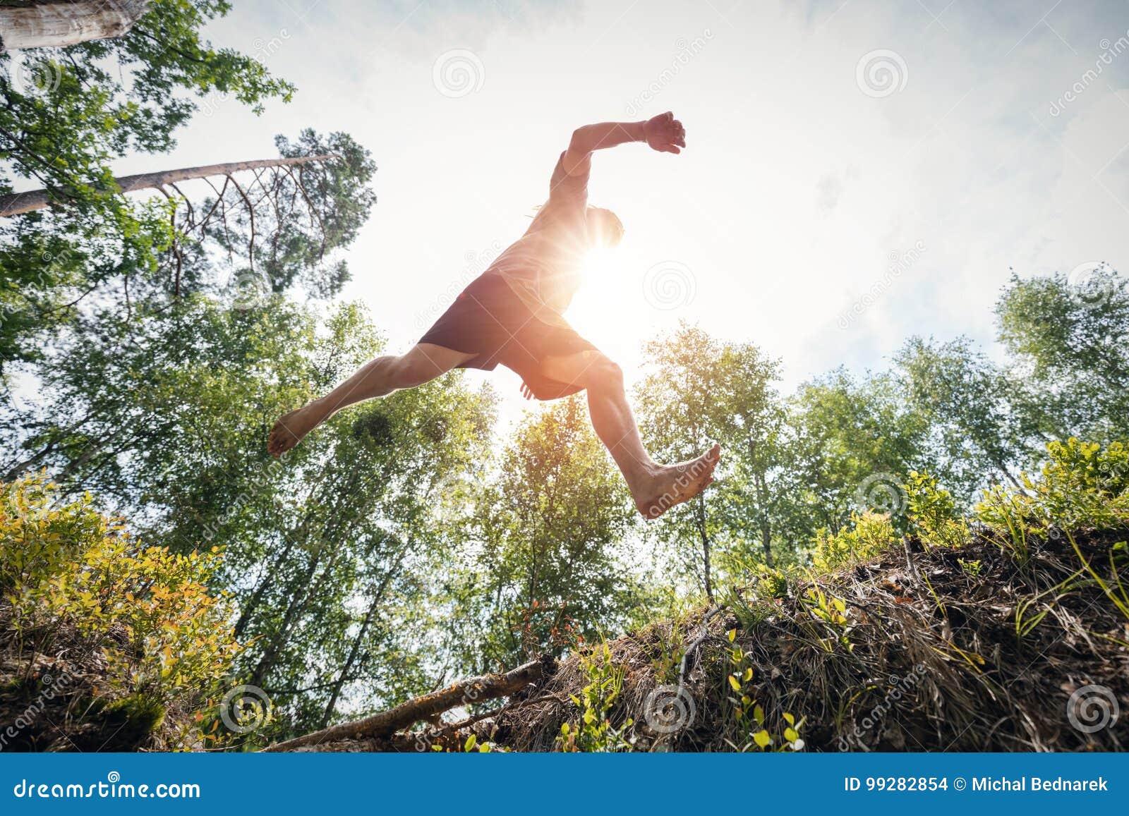 Hombre joven que salta en el bosque