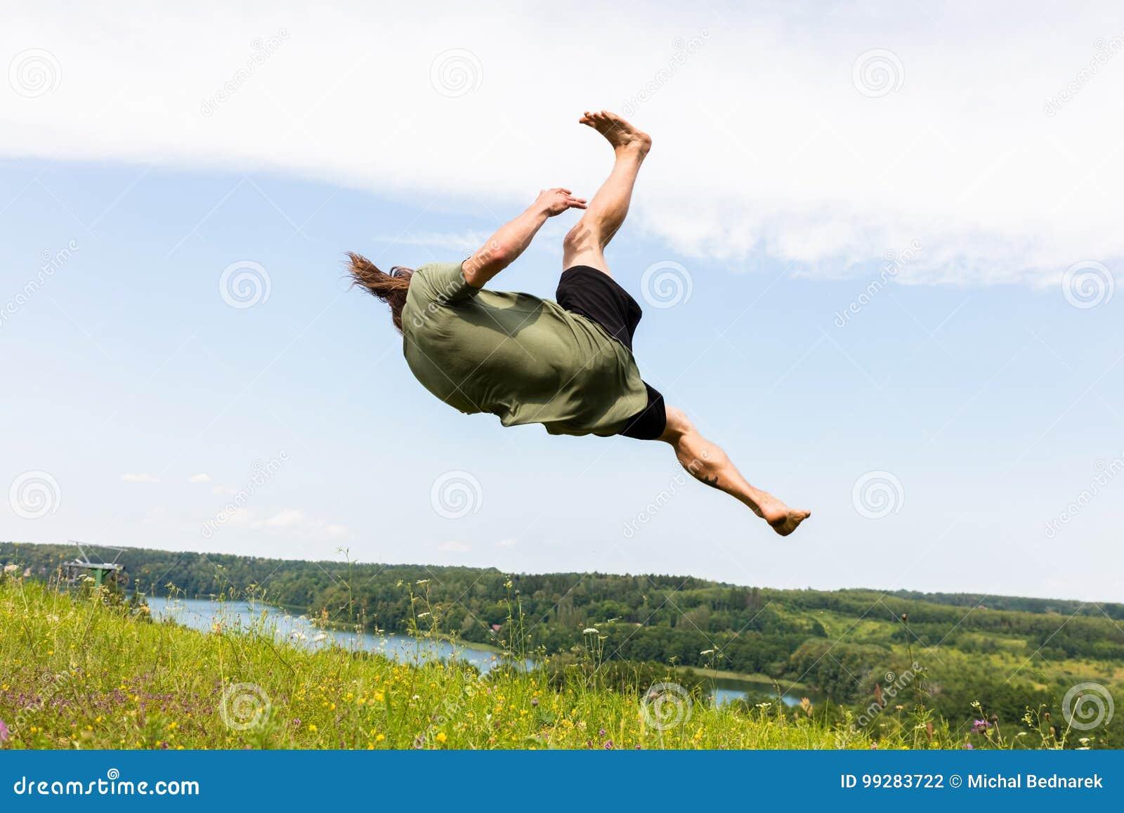 Hombre joven que salta en una colina
