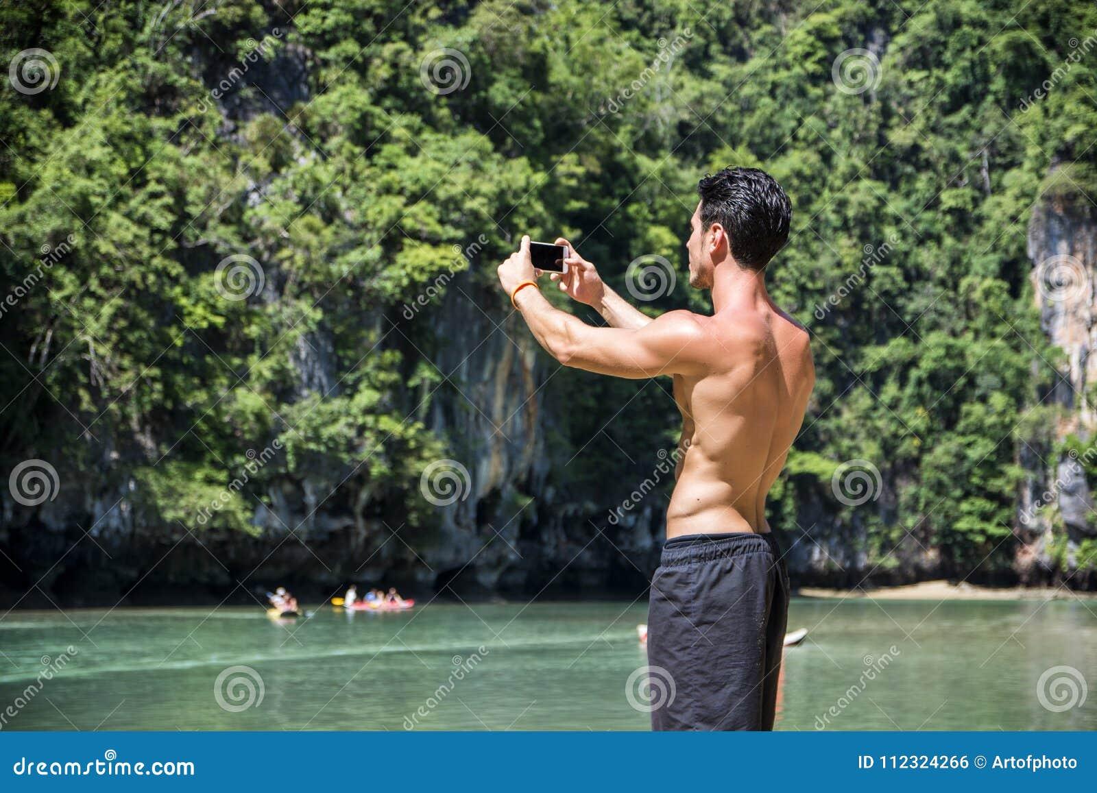 Hombre joven que se coloca en el borde del océano
