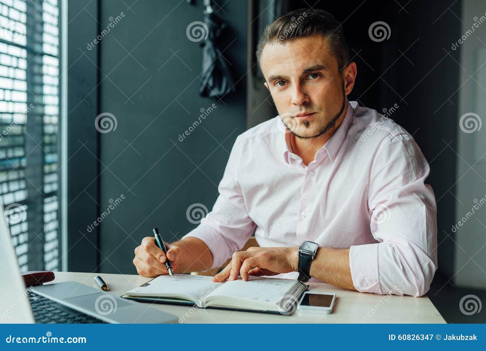 Hombre joven que se sienta en café y que añade la nueva reunión en su calenda