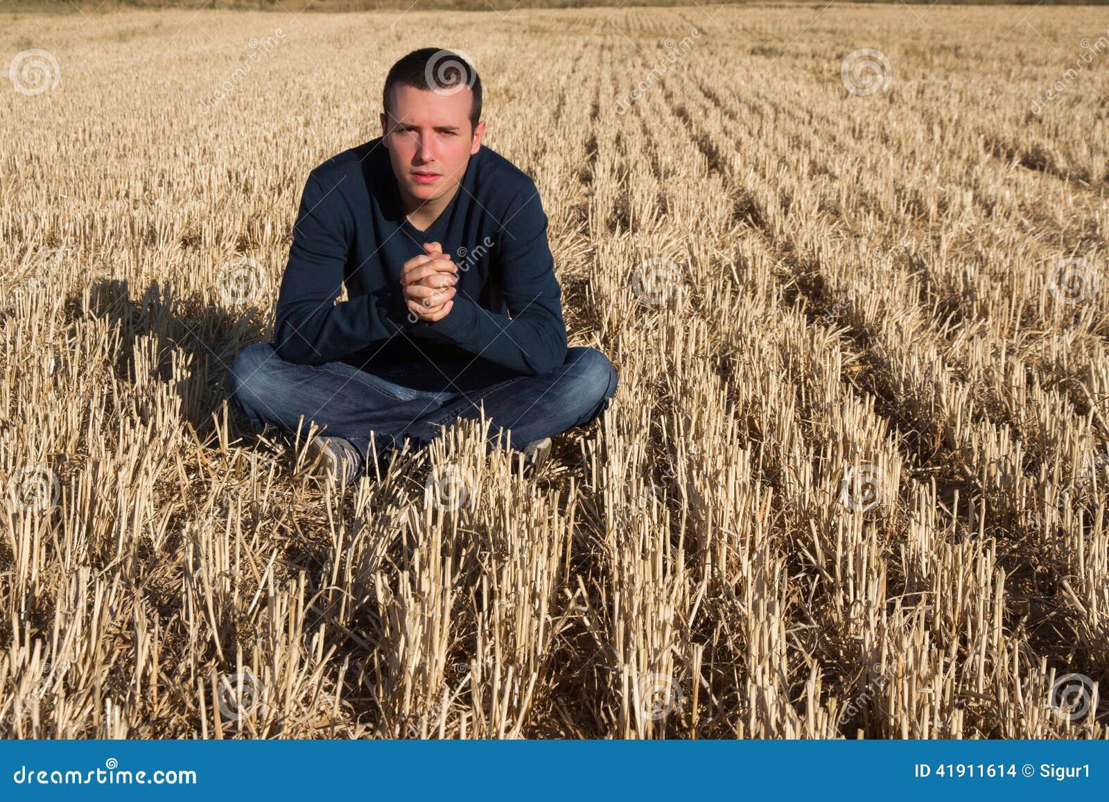 Hombre joven que se sienta en campo
