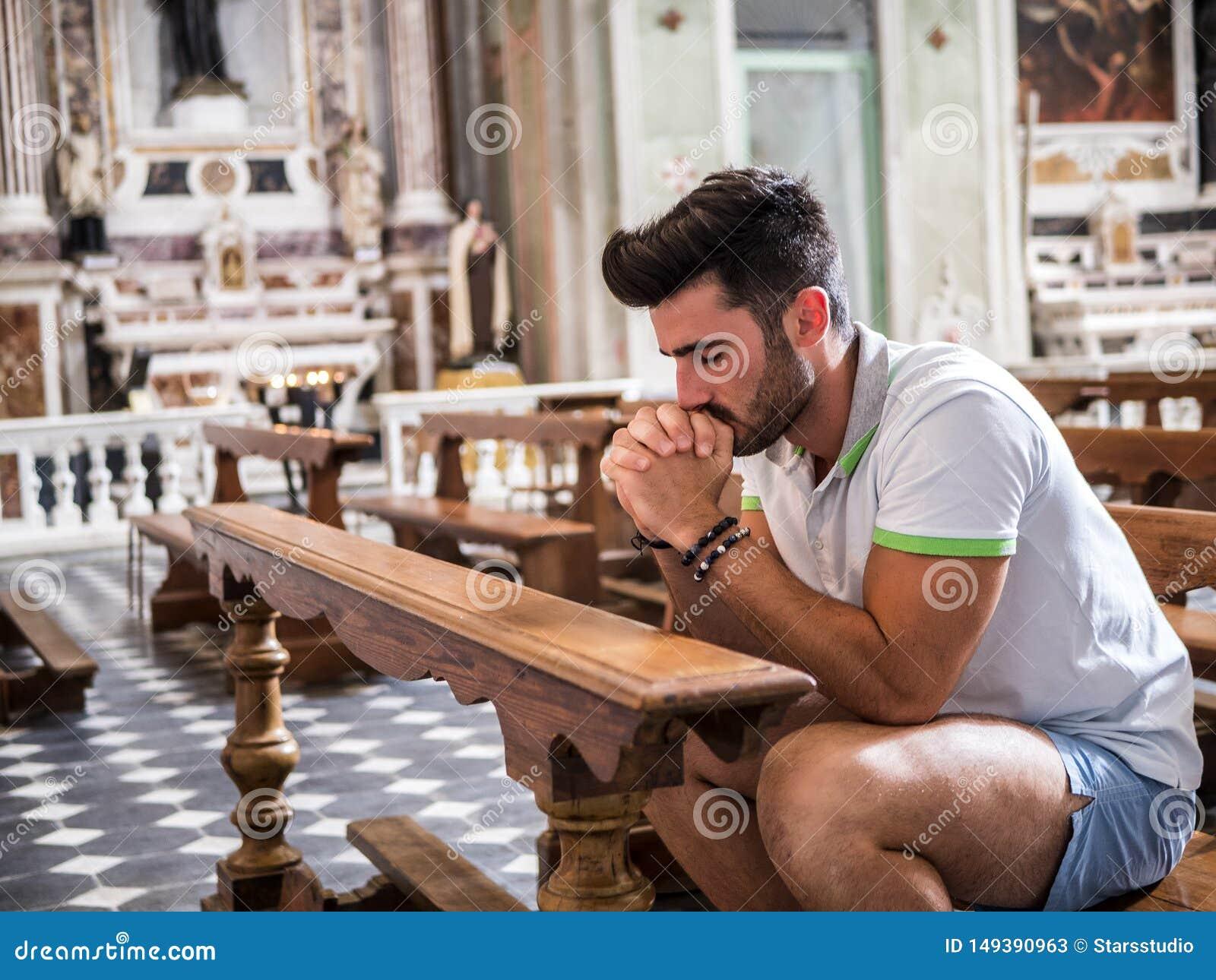 Hombre joven que se sienta en la rogaci?n de la iglesia