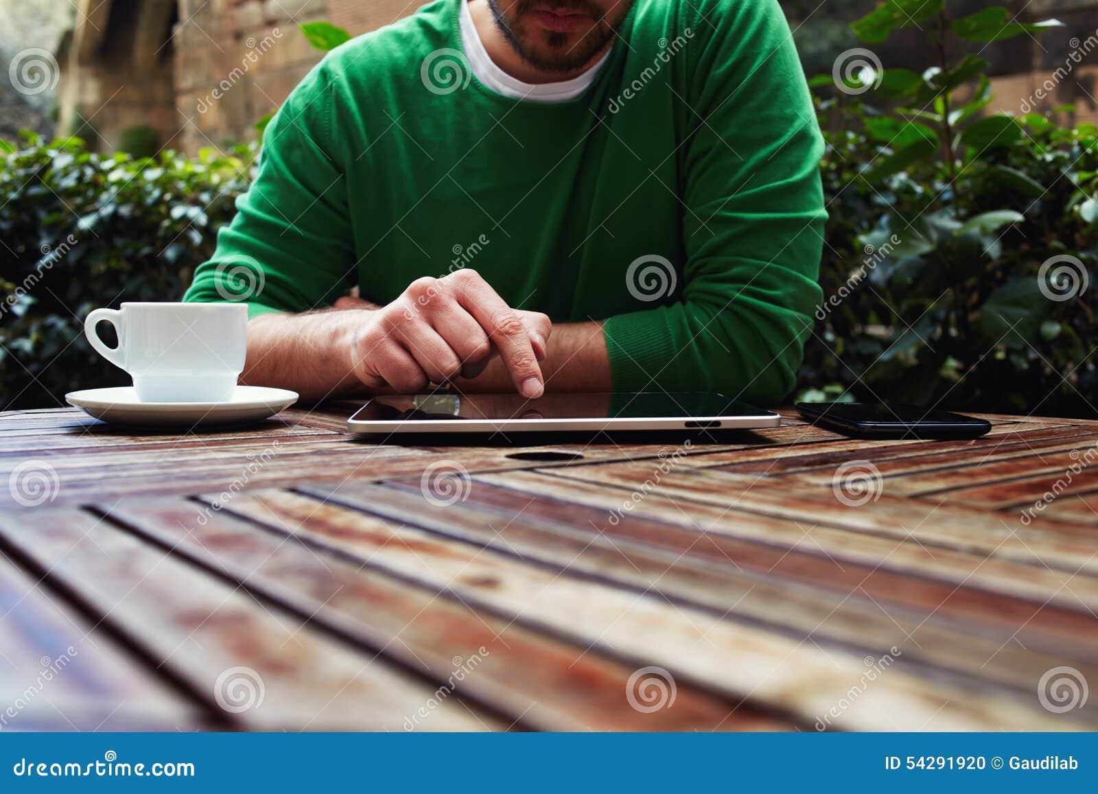 Hombre joven que se sienta en la tabla con la taza de café