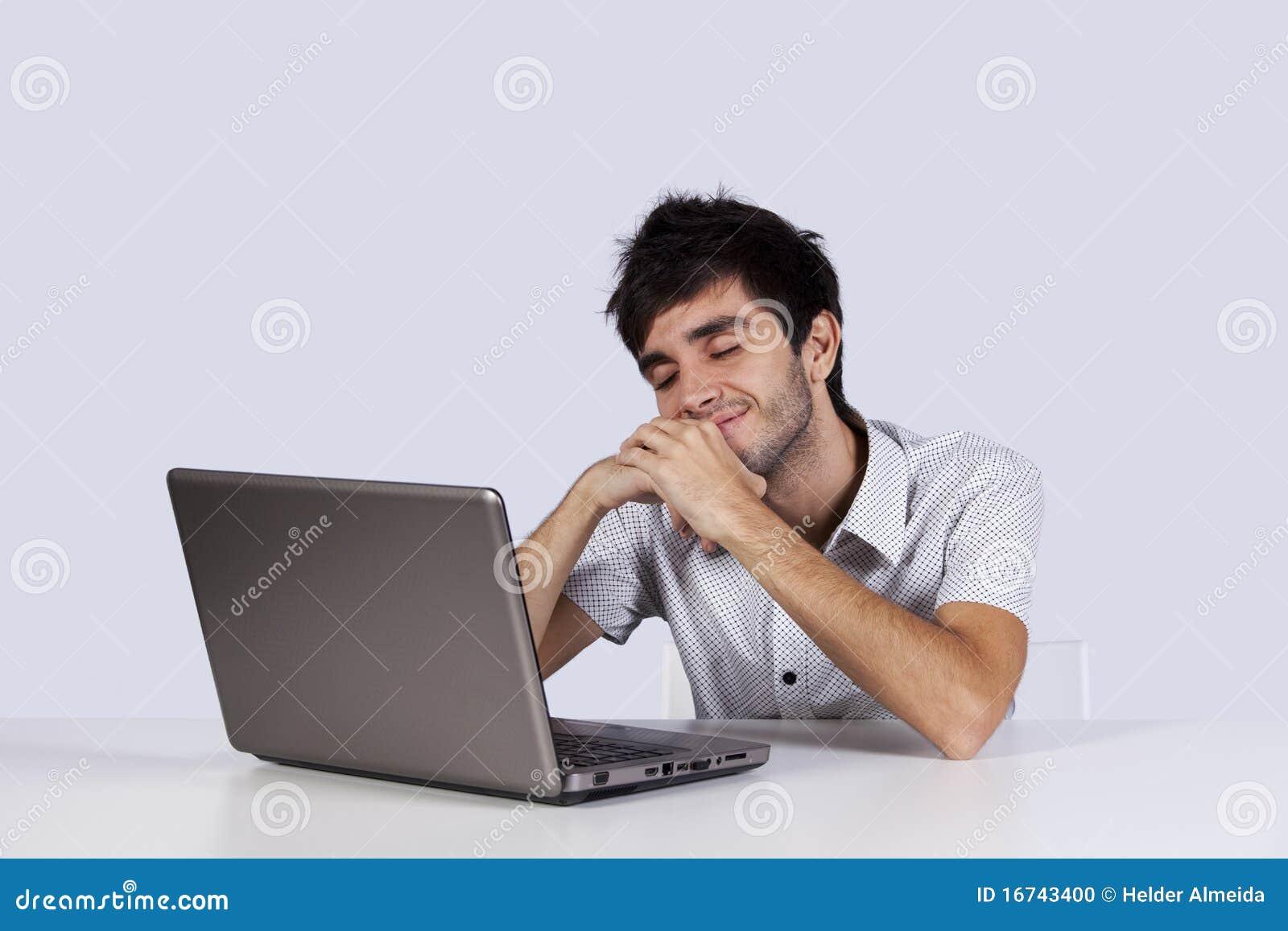Hombre joven que soña delante de su computadora portátil