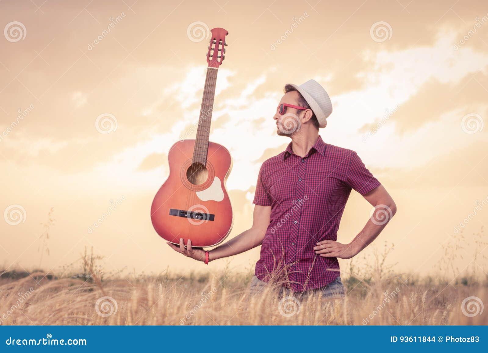 Hombre joven que sostiene la guitarra en el campo