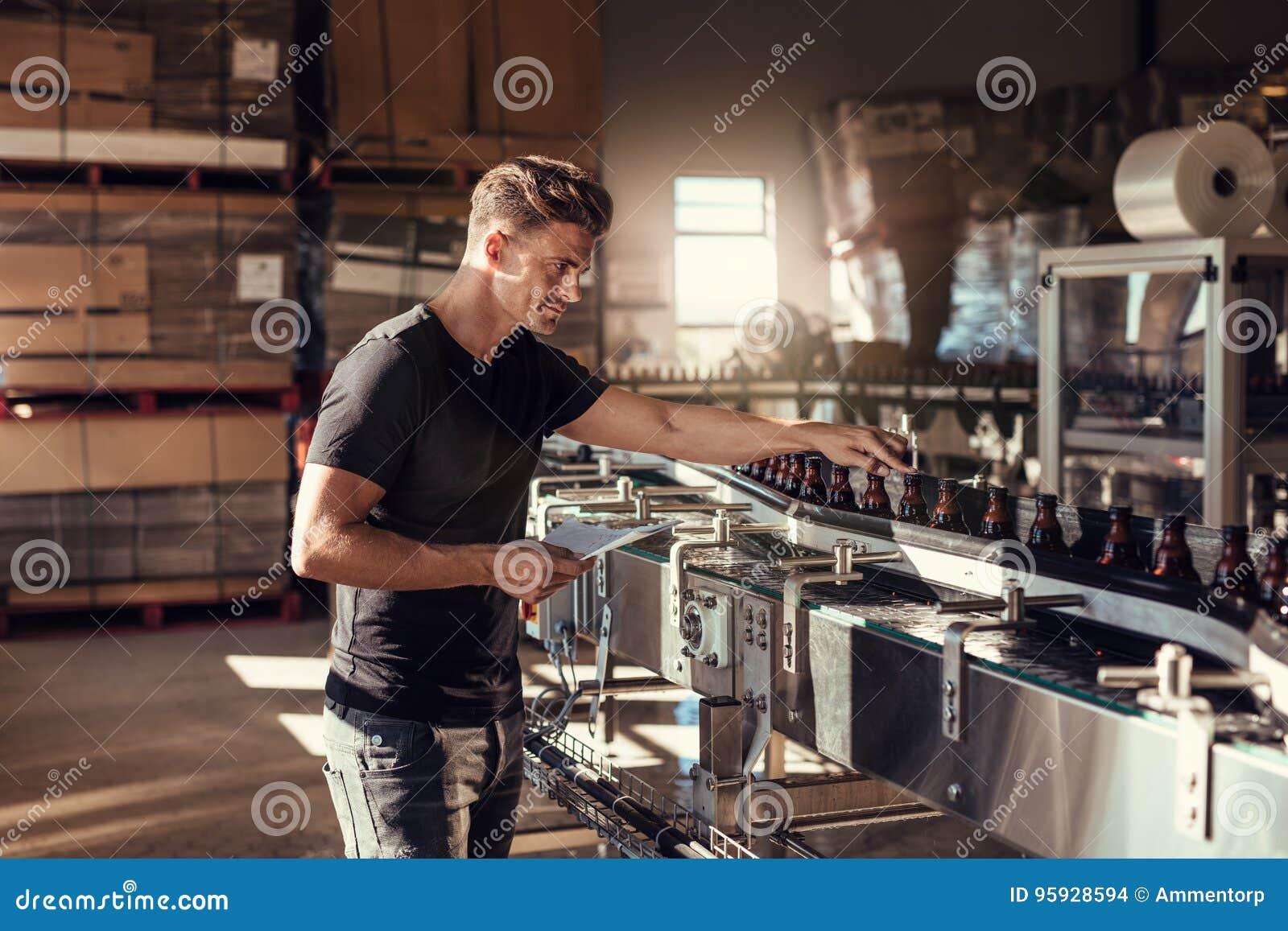 Hombre joven que supervisa la producción de la cerveza en la cervecería