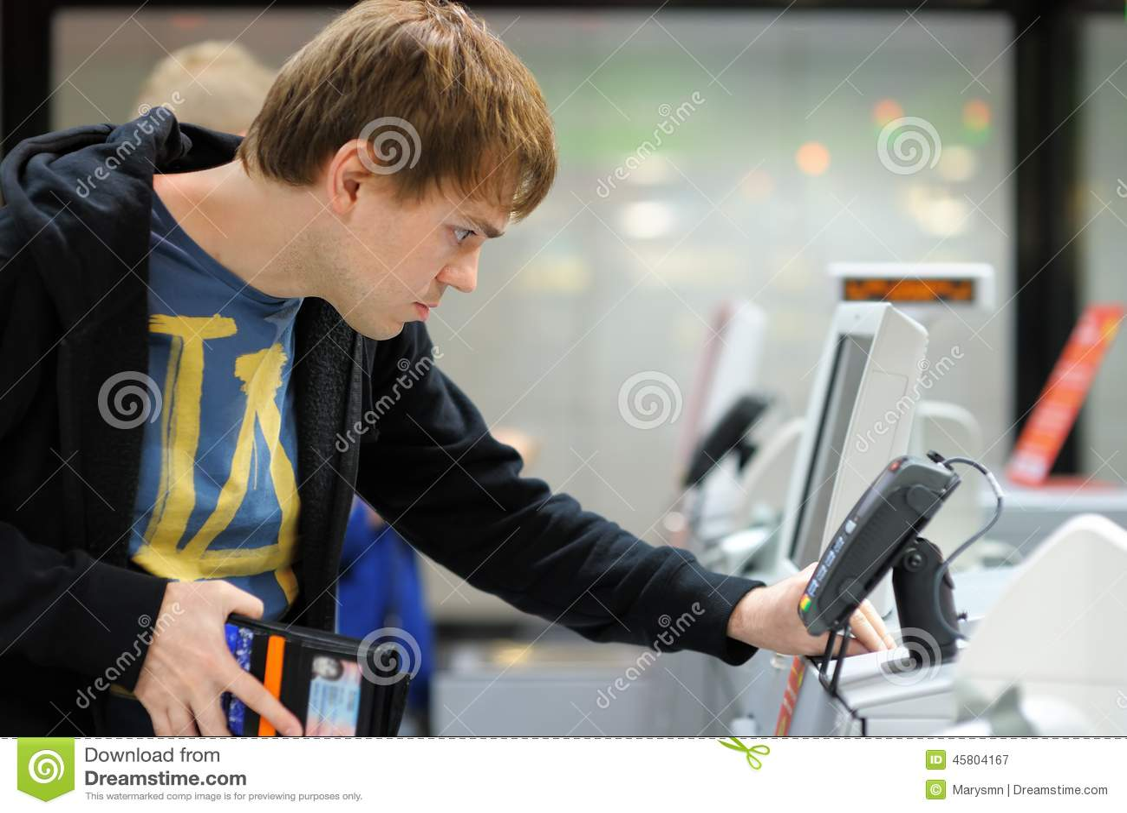 Hombre joven que usa el terminal de la posición en la tienda
