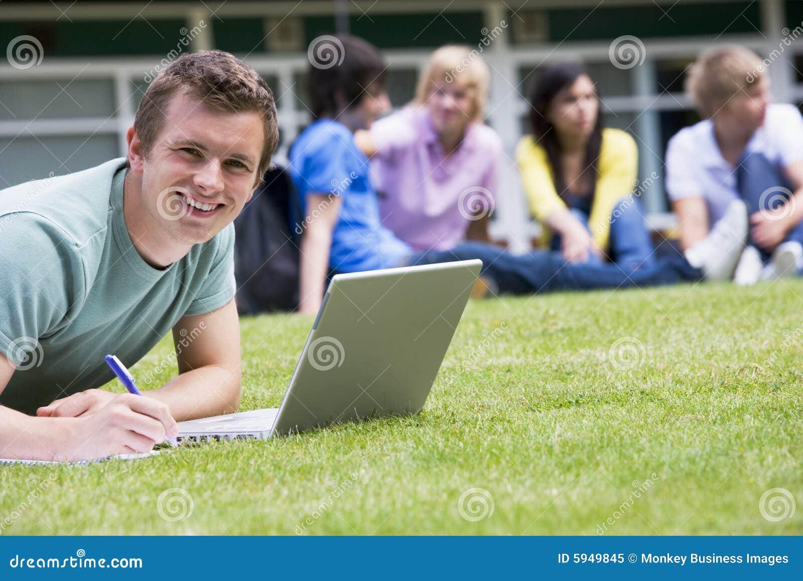 Hombre joven que usa la computadora portátil en césped del campus