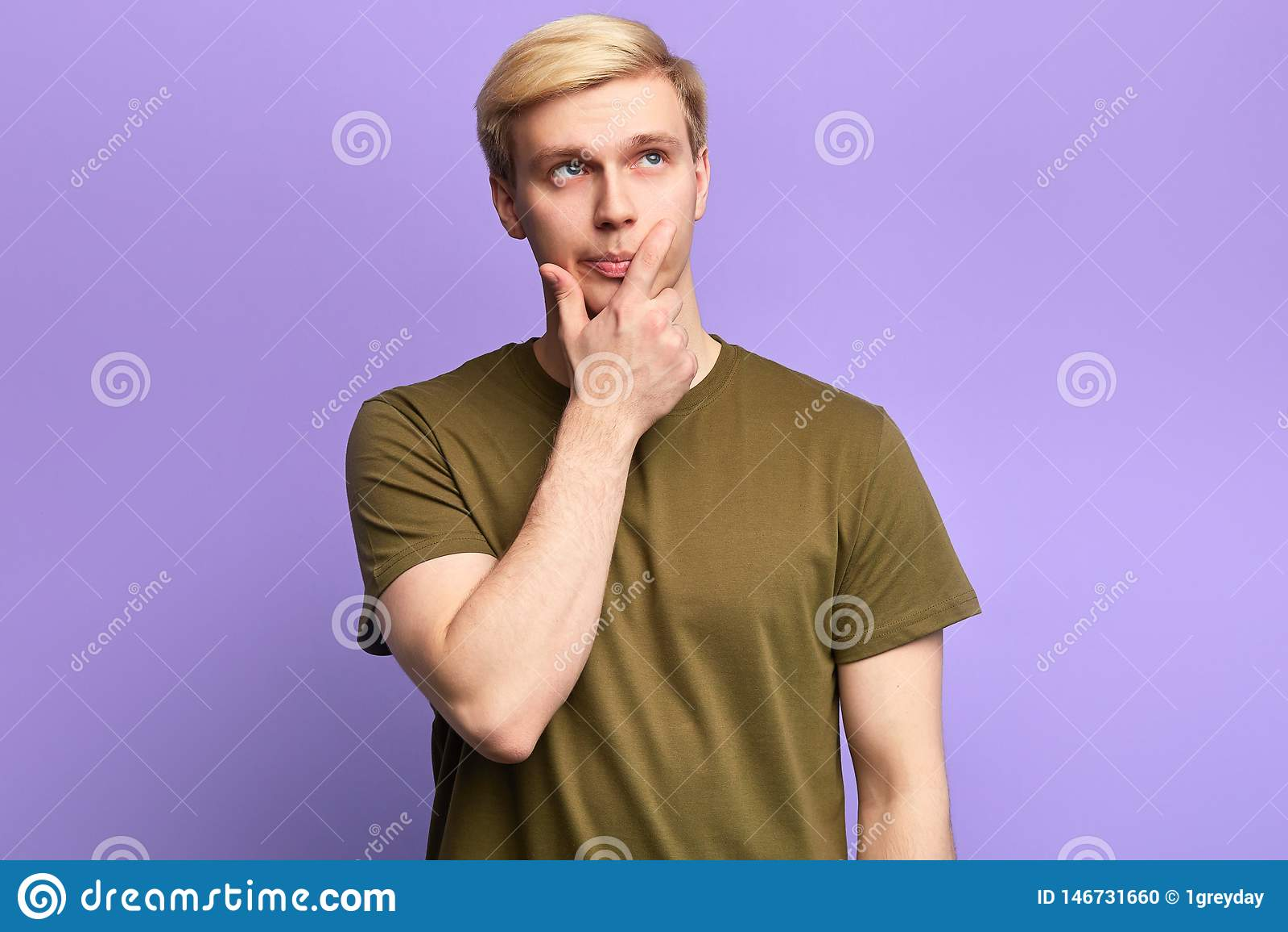 Hombre joven serio hermoso que mira para arriba con mirada pensativa