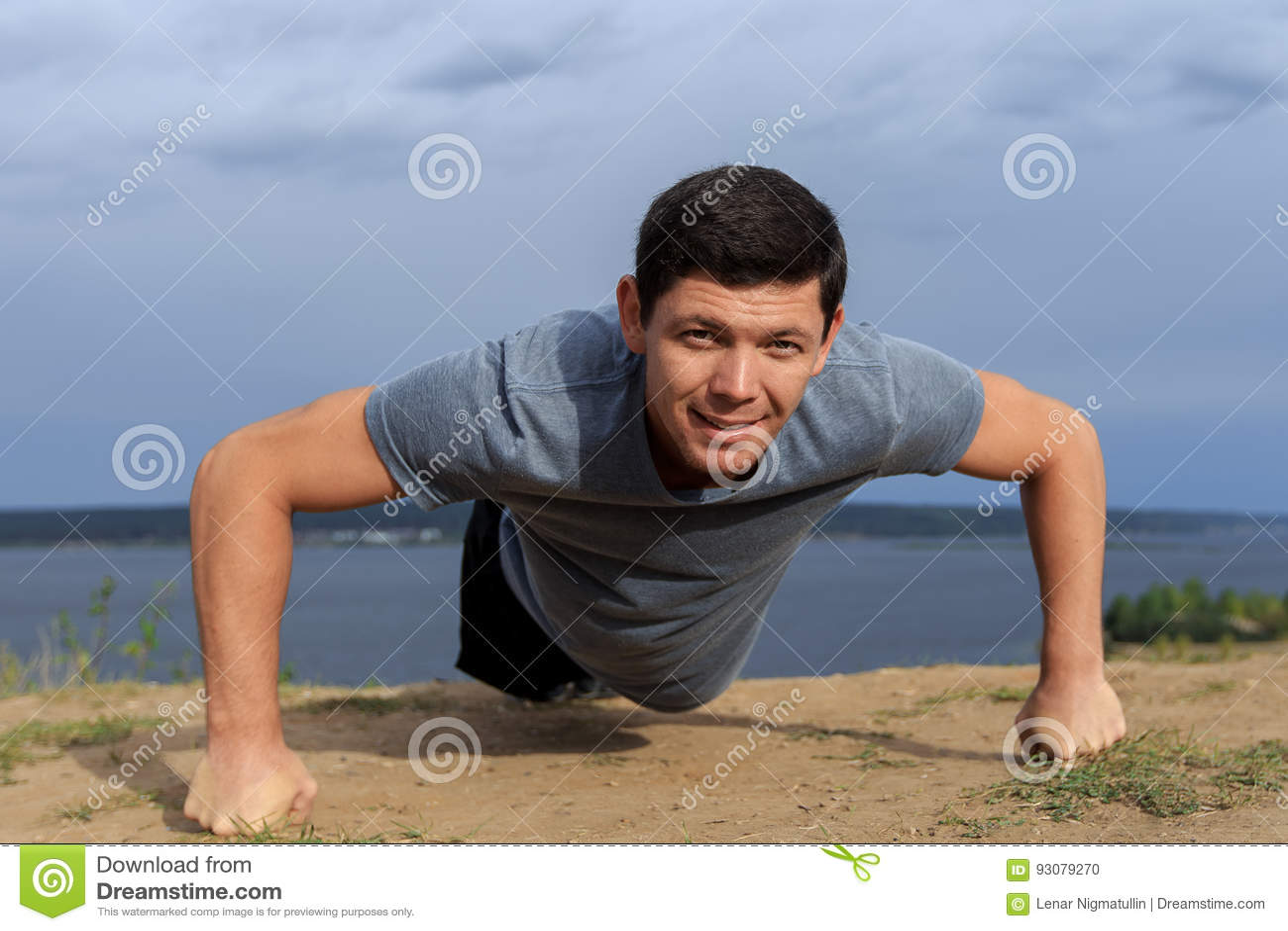 Hombre joven sonriente que hace pectorales al aire libre