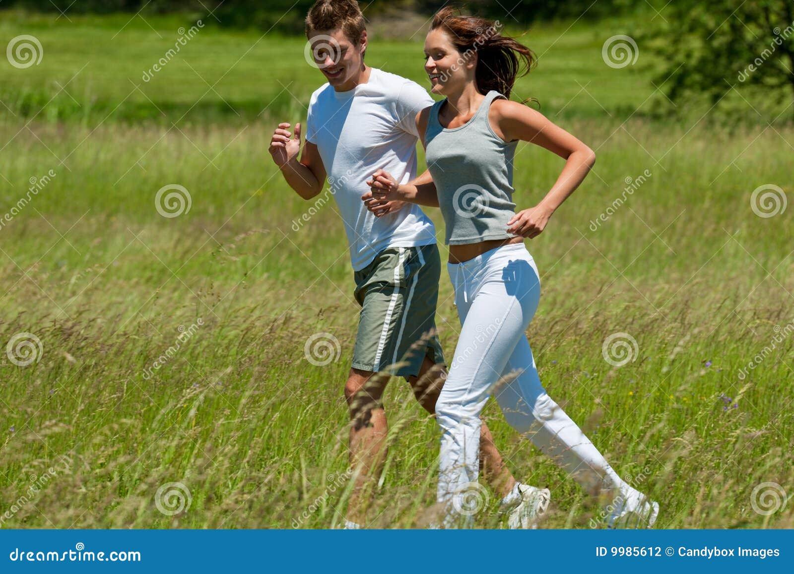 Hombre joven y mujer que activan en un prado