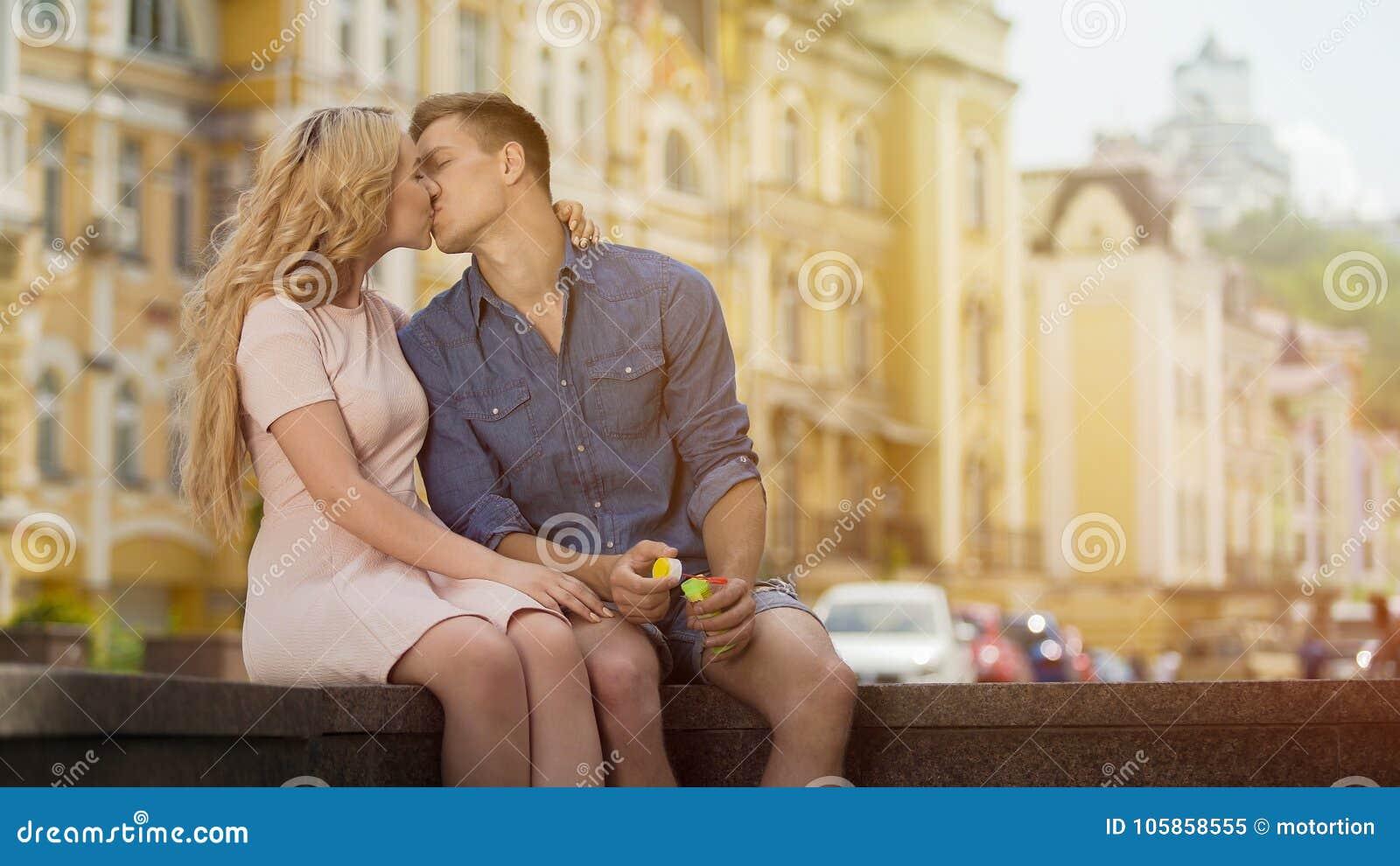 Hombre joven y mujer que se besan la fecha, la felicidad y el amor románticos dulces, par