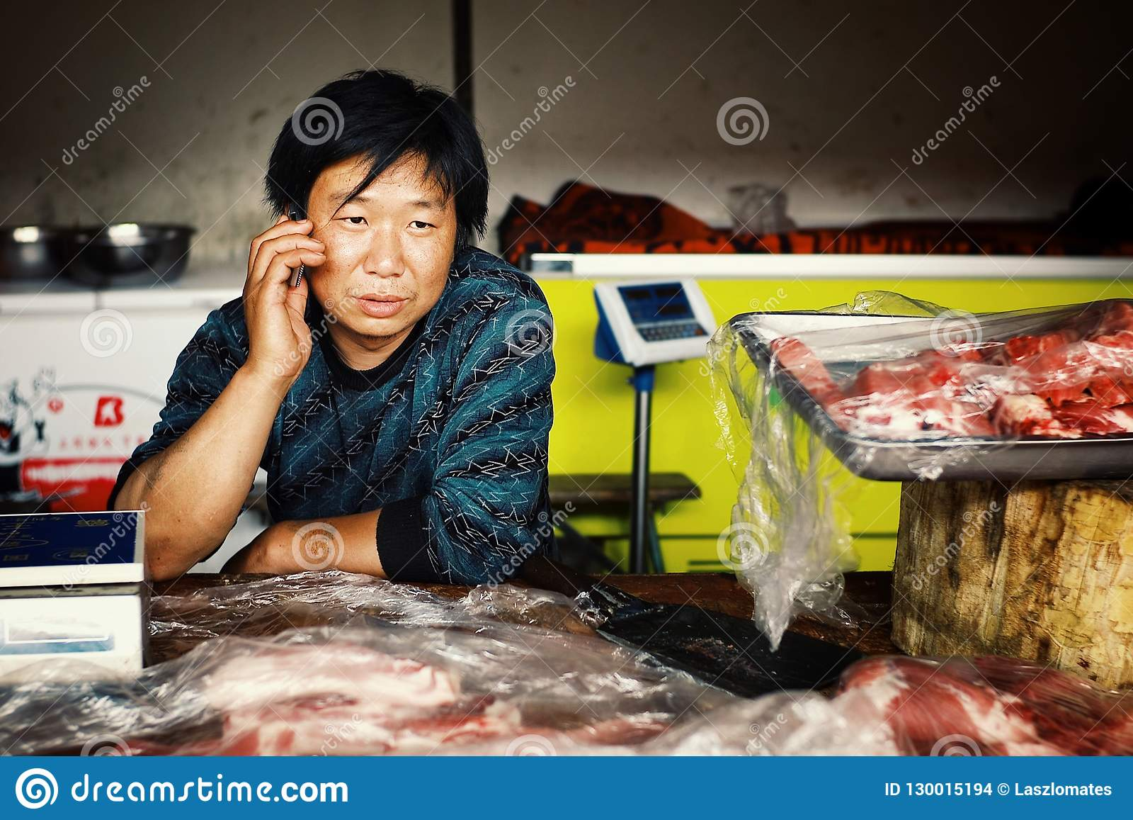 Hombre local en el mercado que vende la carne tajada mientras que en el teléfono