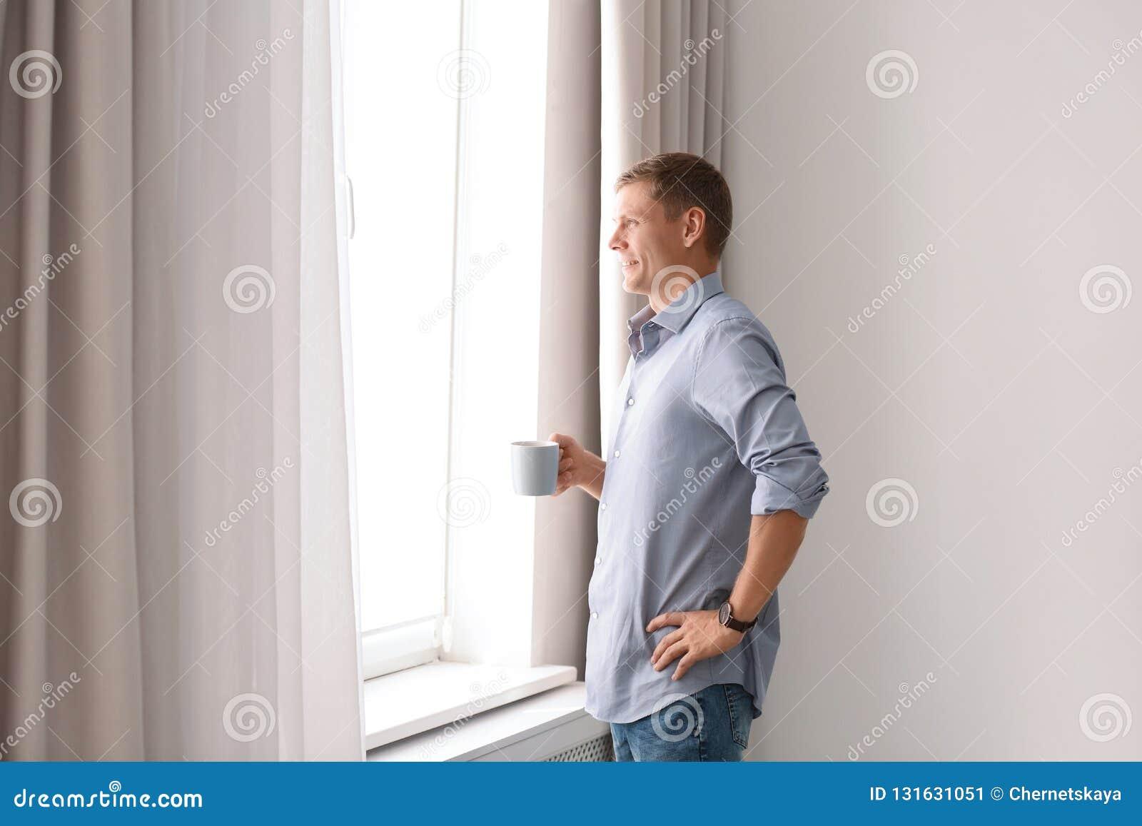 Hombre maduro con la taza de bebida cerca de la ventana con las cortinas abiertas en casa