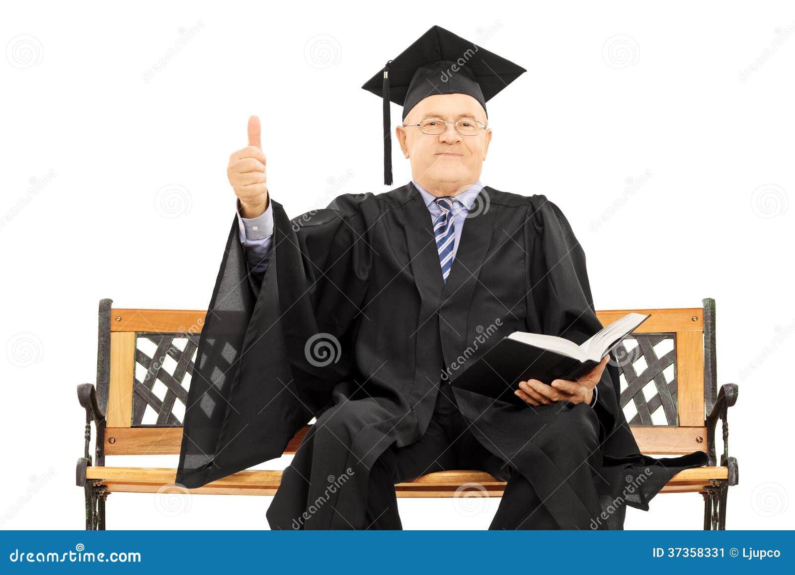 Hombre maduro en vestido de la graduación en el banco que da un pulgar para arriba