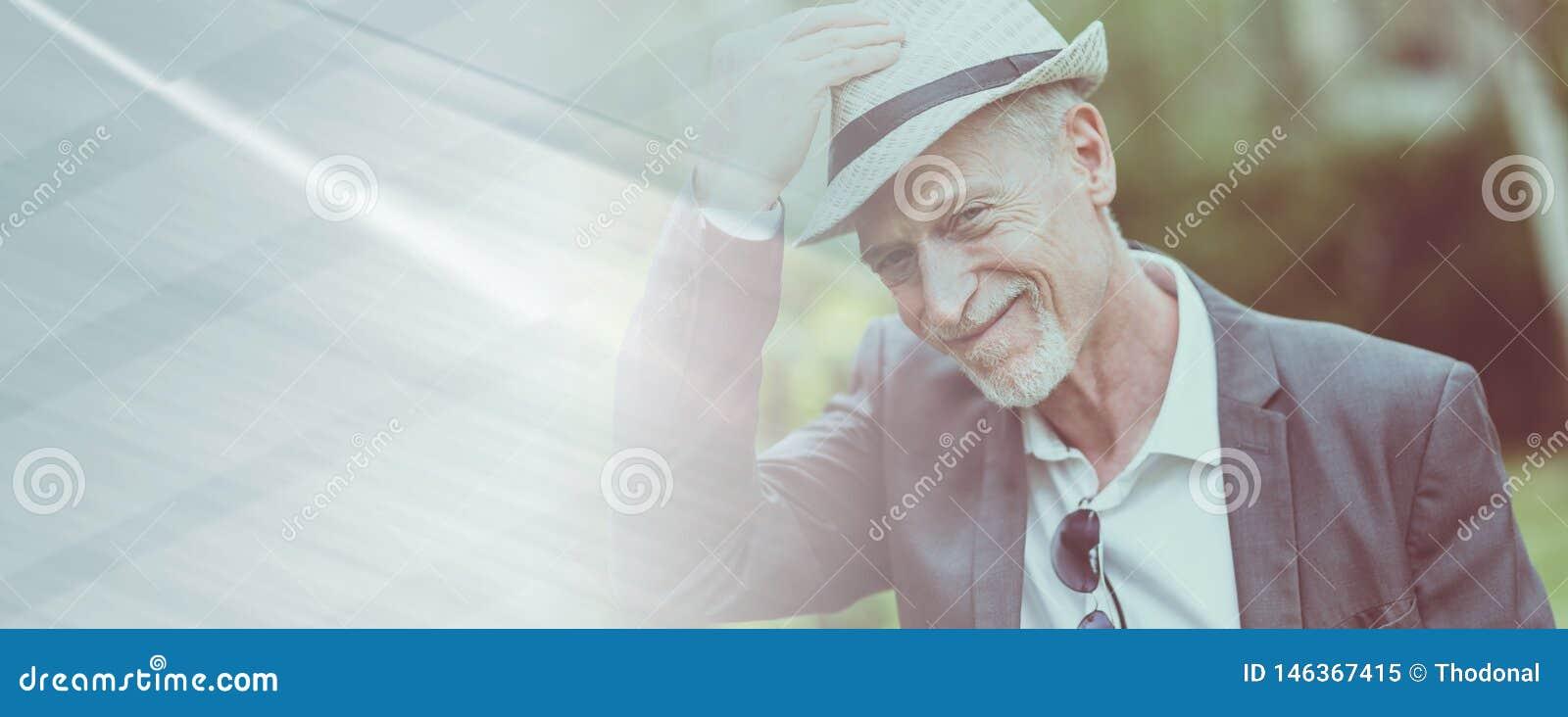 Hombre maduro feliz que lleva un sombrero, efecto luminoso