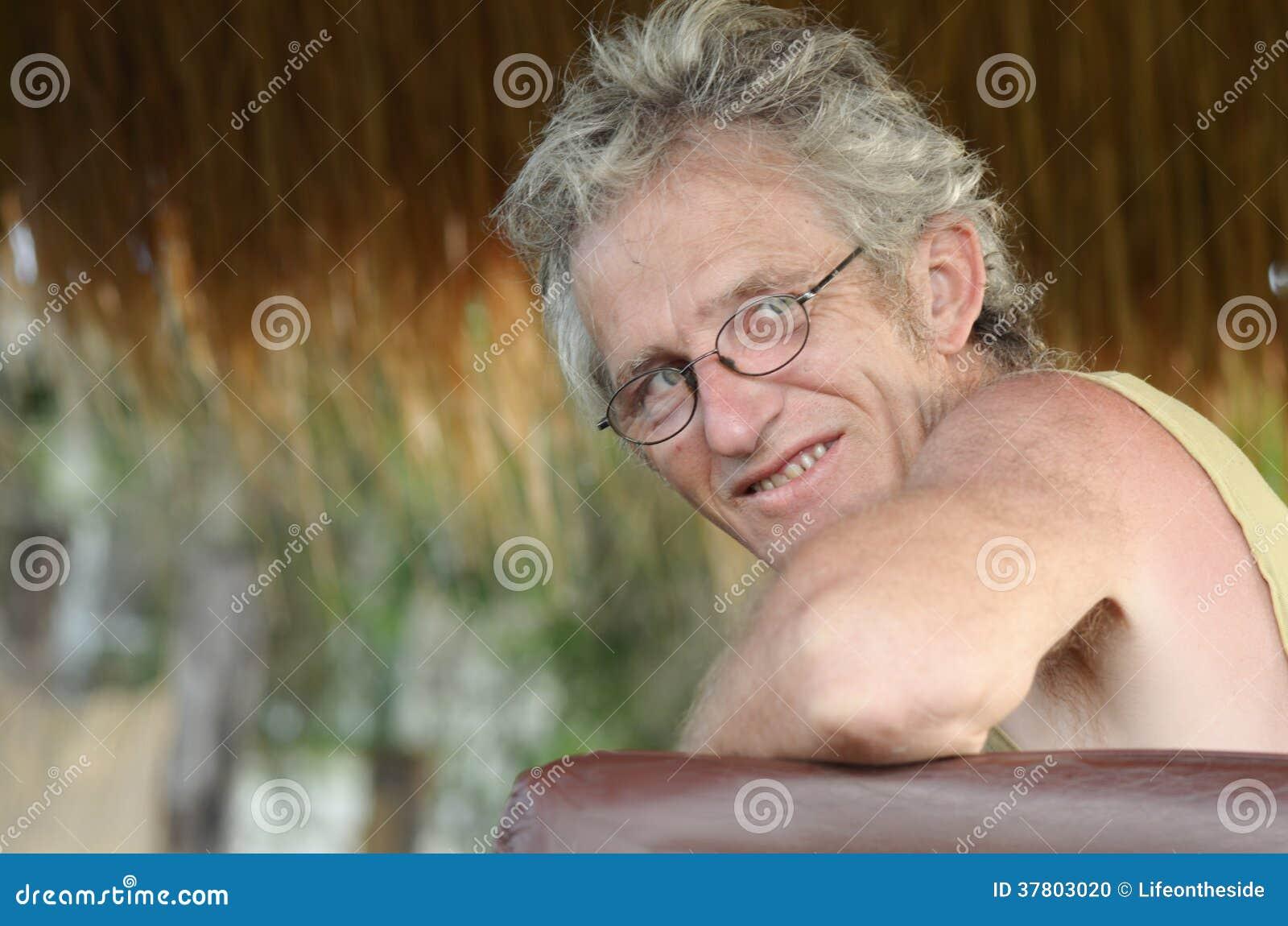 Hombre maduro mayor y sonrisa relajada de las gafas