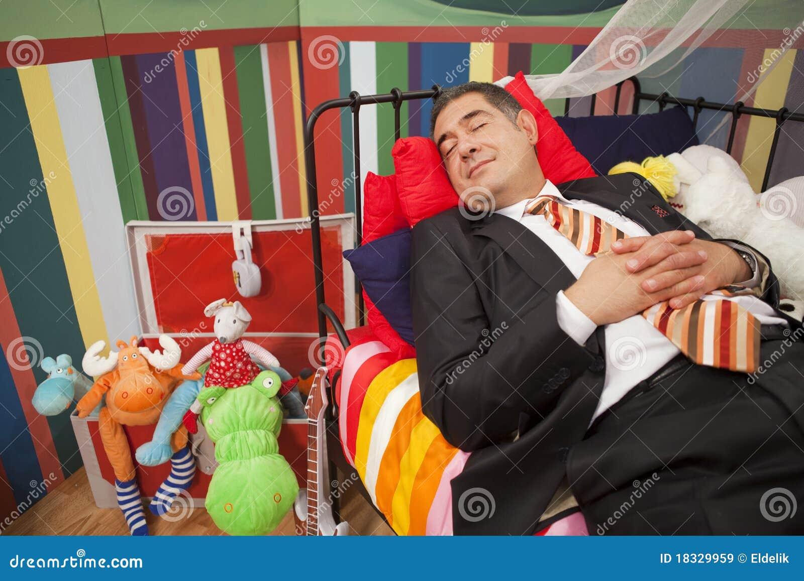 Hombre maduro que duerme en cama del niño