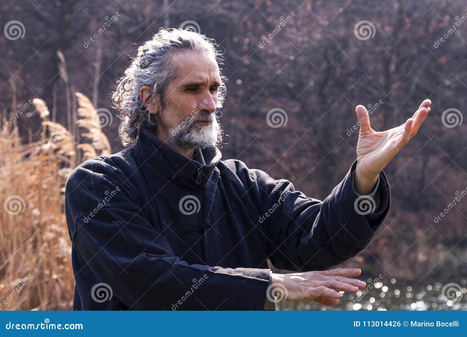 Hombre maduro que practica la disciplina de Tai Chi al aire libre
