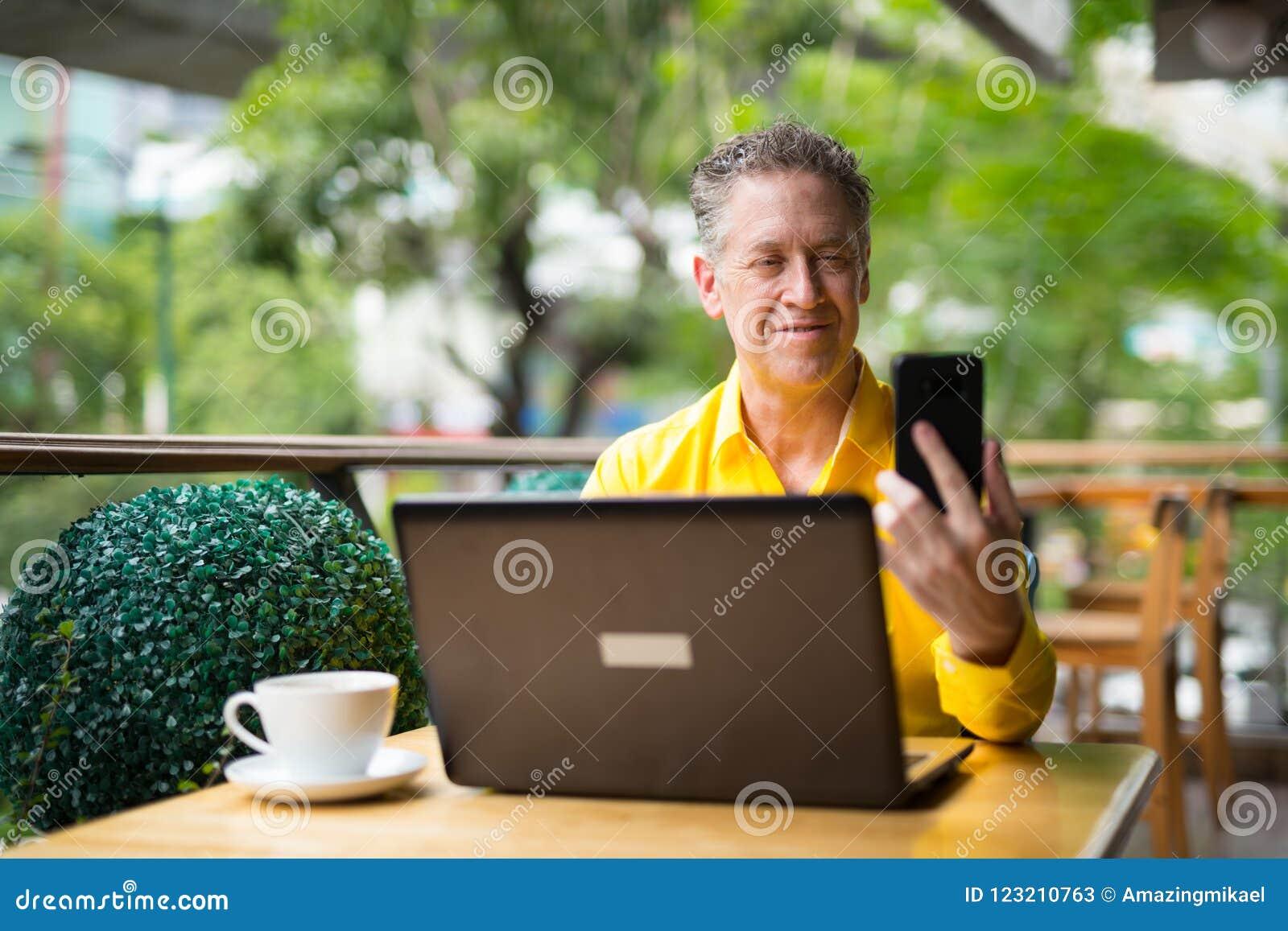 Hombre maduro que usa el ordenador portátil y el teléfono móvil