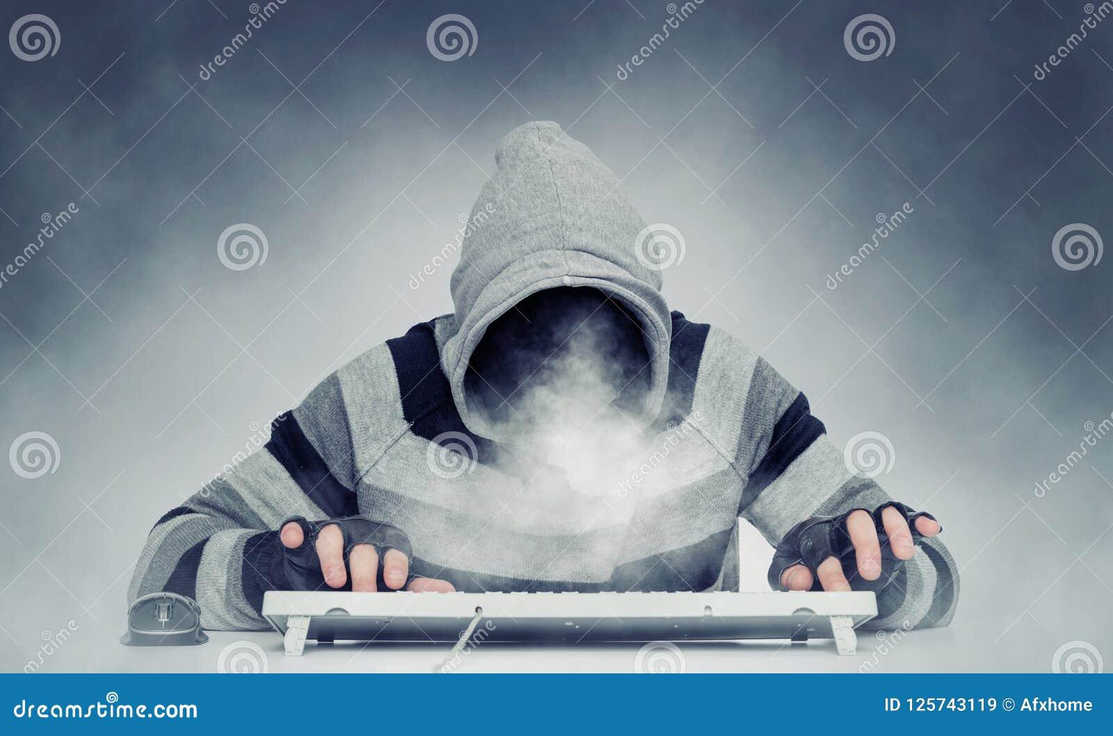 Hombre malvado del pirata informático anónimo en la sudadera con capucha detrás del teclado, humo en vez de la cara