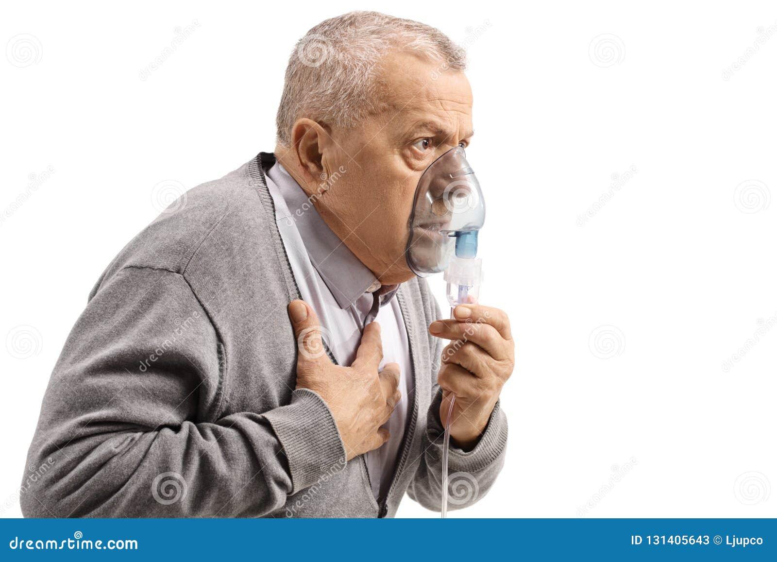 Hombre mayor con asma usando un inhalador y sostenerse el pecho