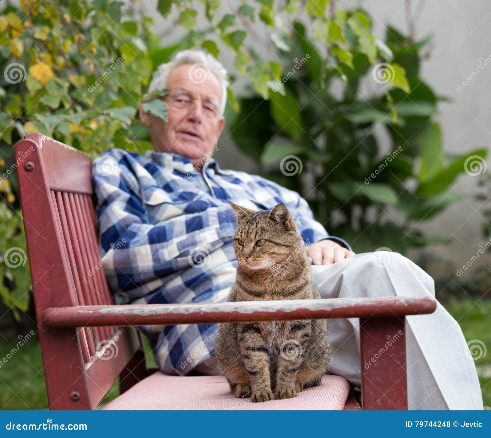 Hombre mayor con el gato en patio