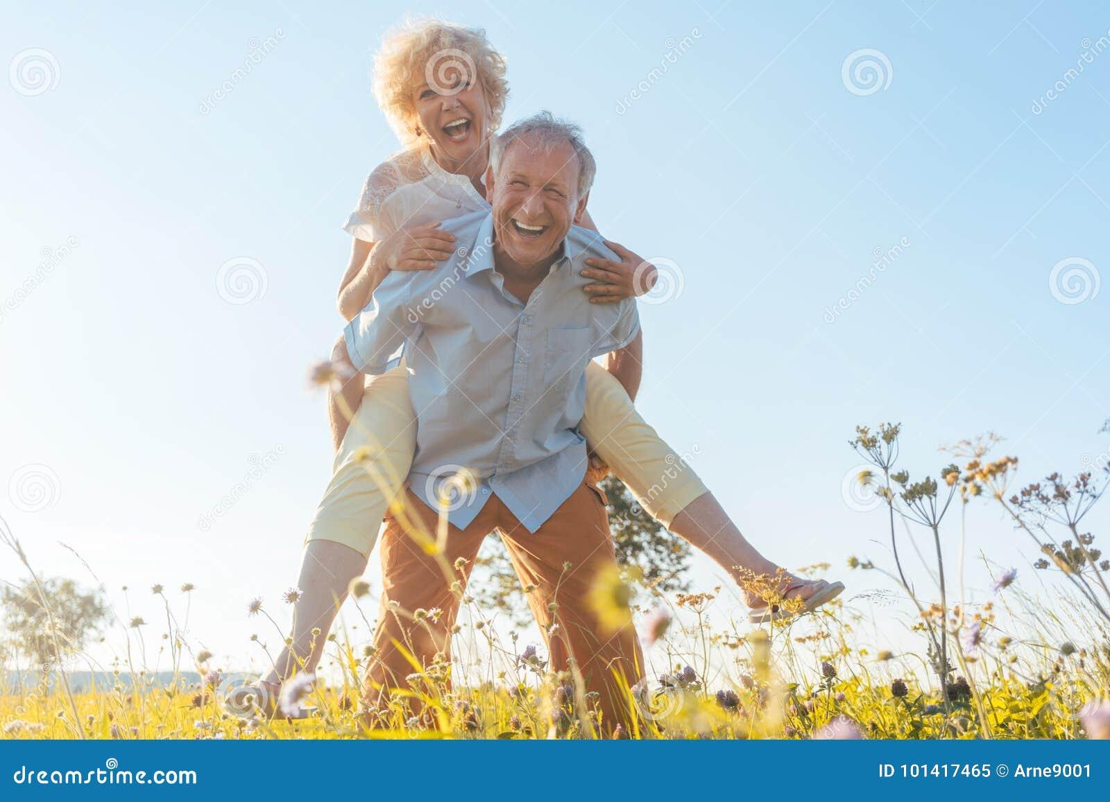 Hombre mayor feliz que ríe mientras que lleva a su socio en el suyo detrás