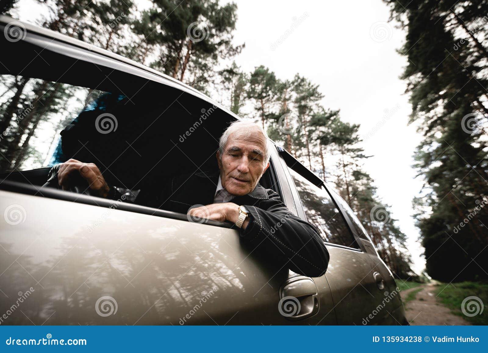 Hombre mayor feliz sonriente y su nuevo coche