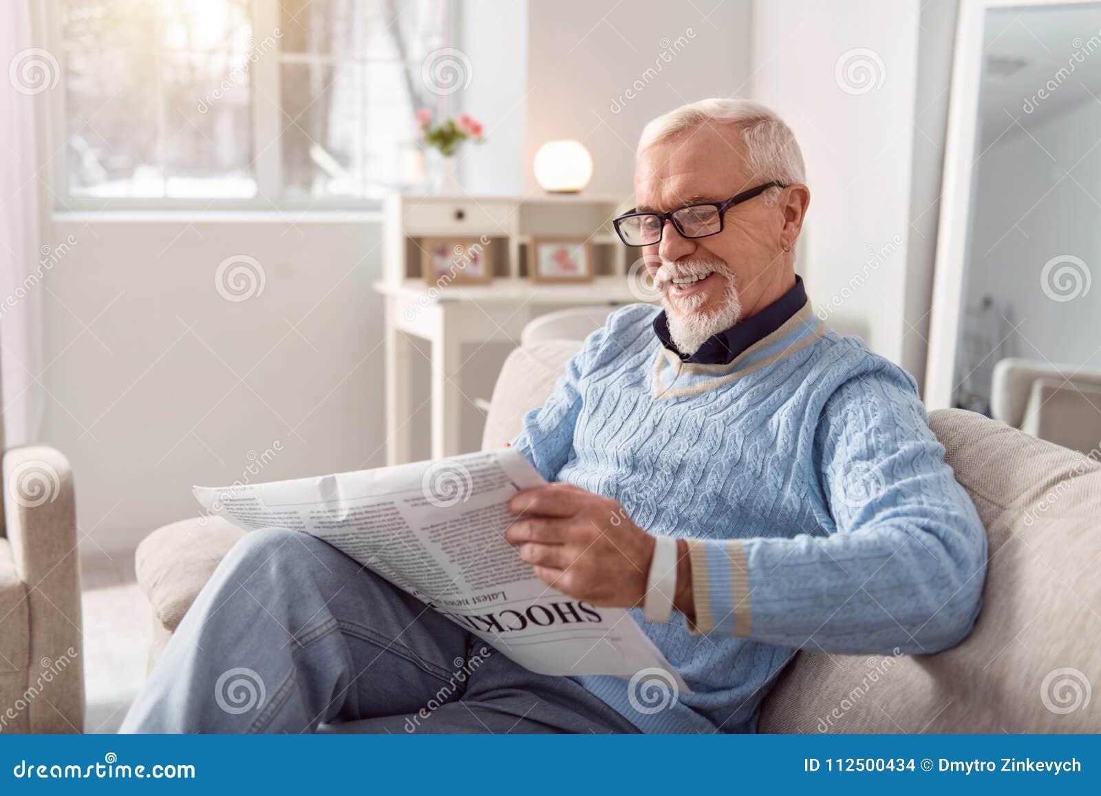 Hombre mayor optimista que sonríe mientras que lee el artículo en periódico