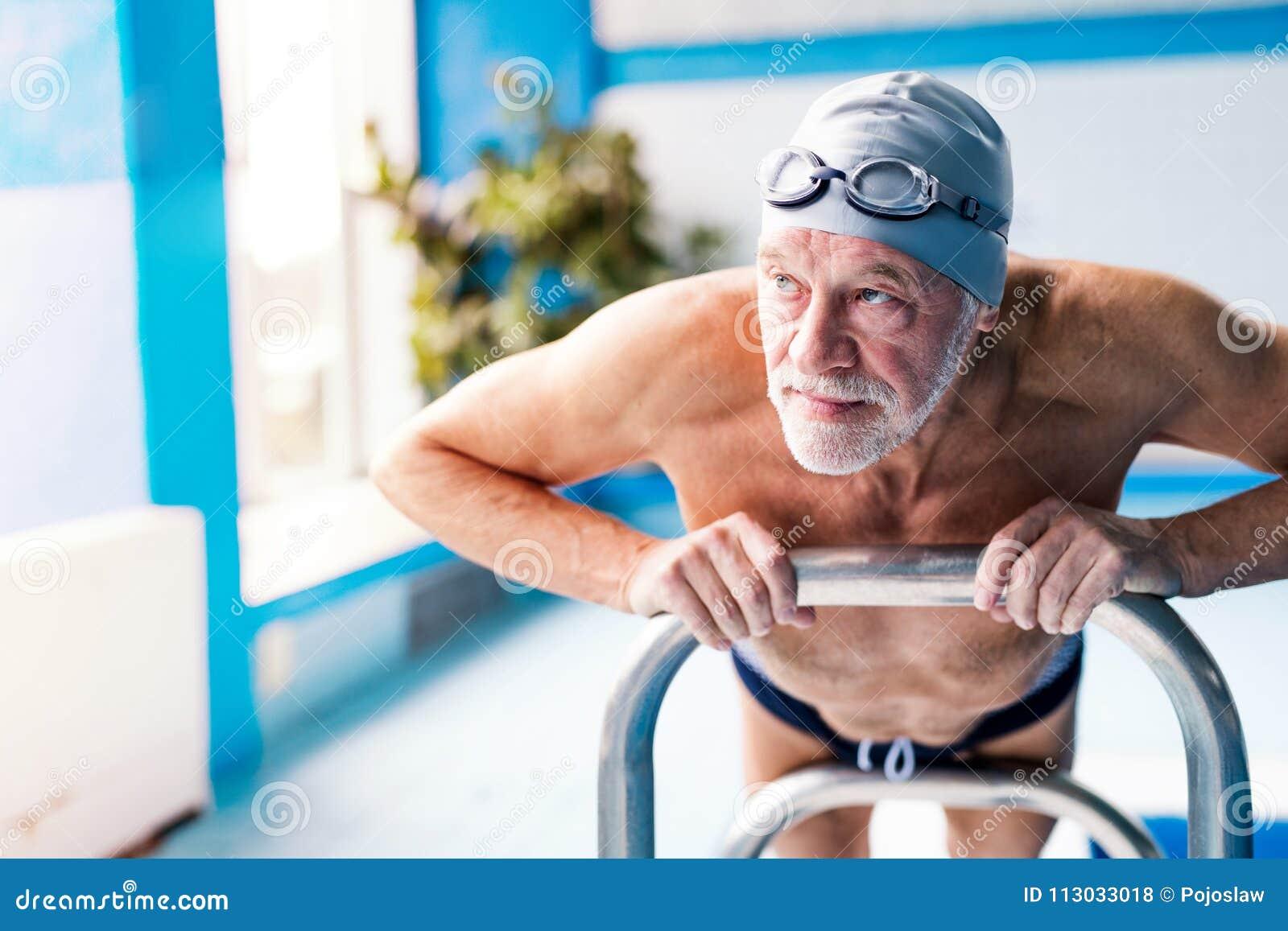 Hombre mayor que estira por la piscina interior