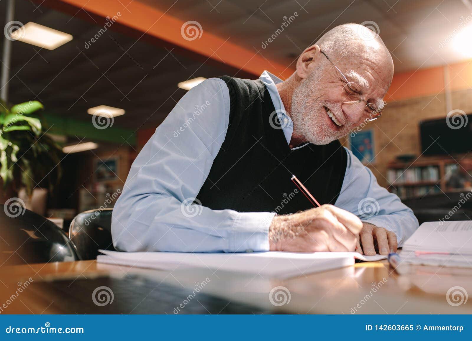 Hombre mayor que hace notas en sala de clase