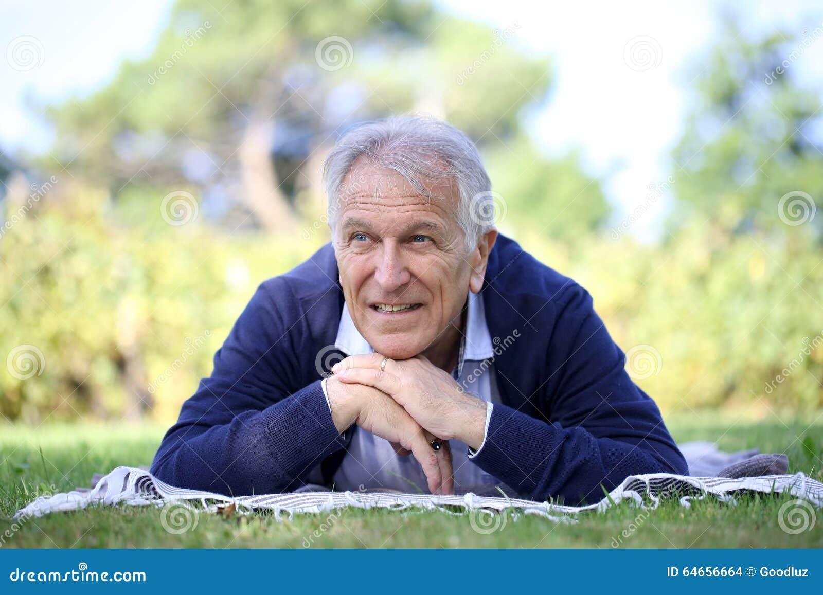 Hombre mayor que miente en la hierba que se relaja