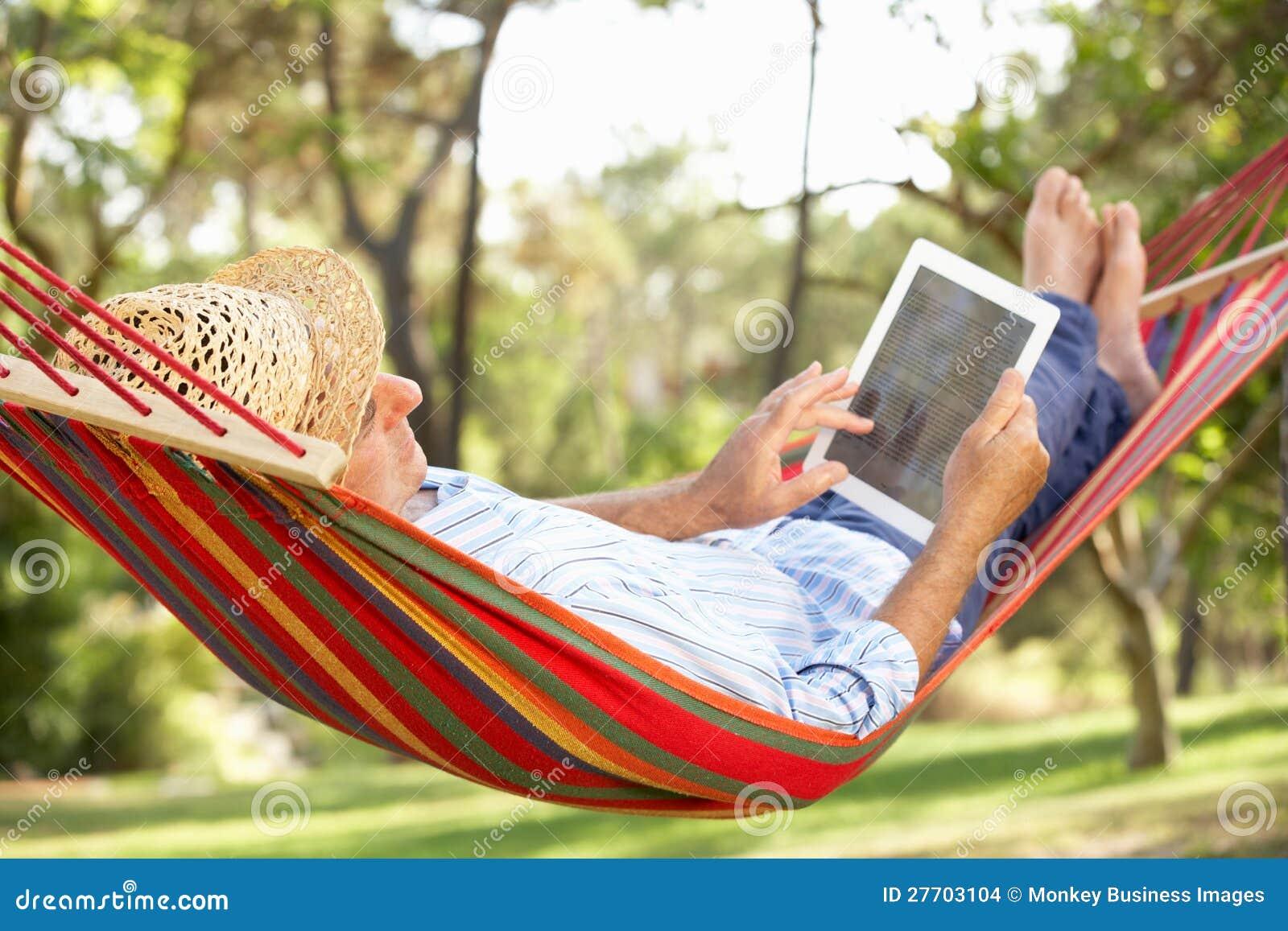 Hombre mayor que se relaja en hamaca con el E-Libro