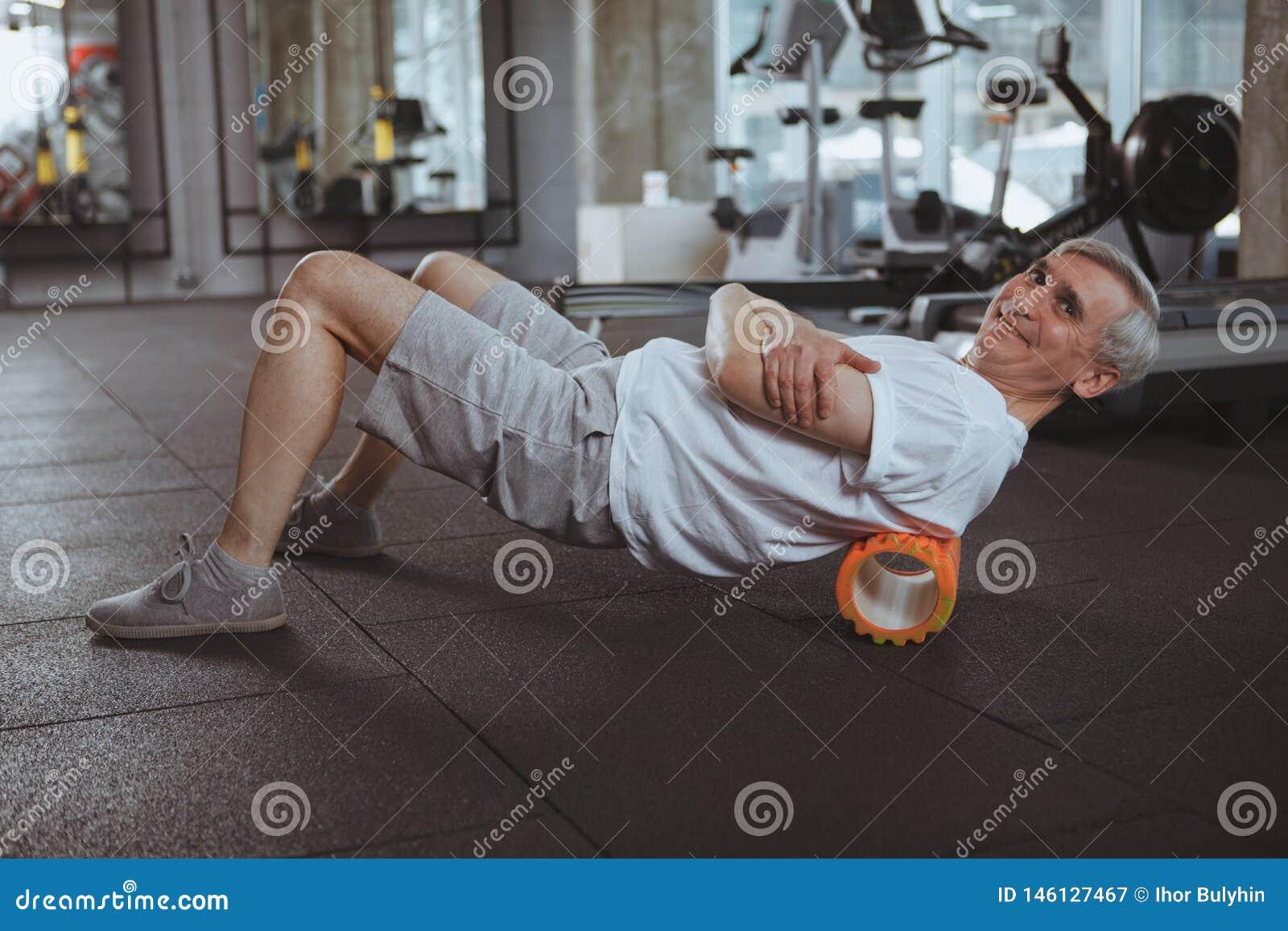 Hombre mayor que se resuelve en el gimnasio