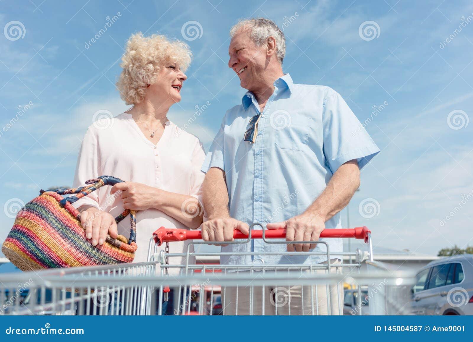 Hombre mayor que sostiene un carro de la compra mientras que mira a su esposa con amor