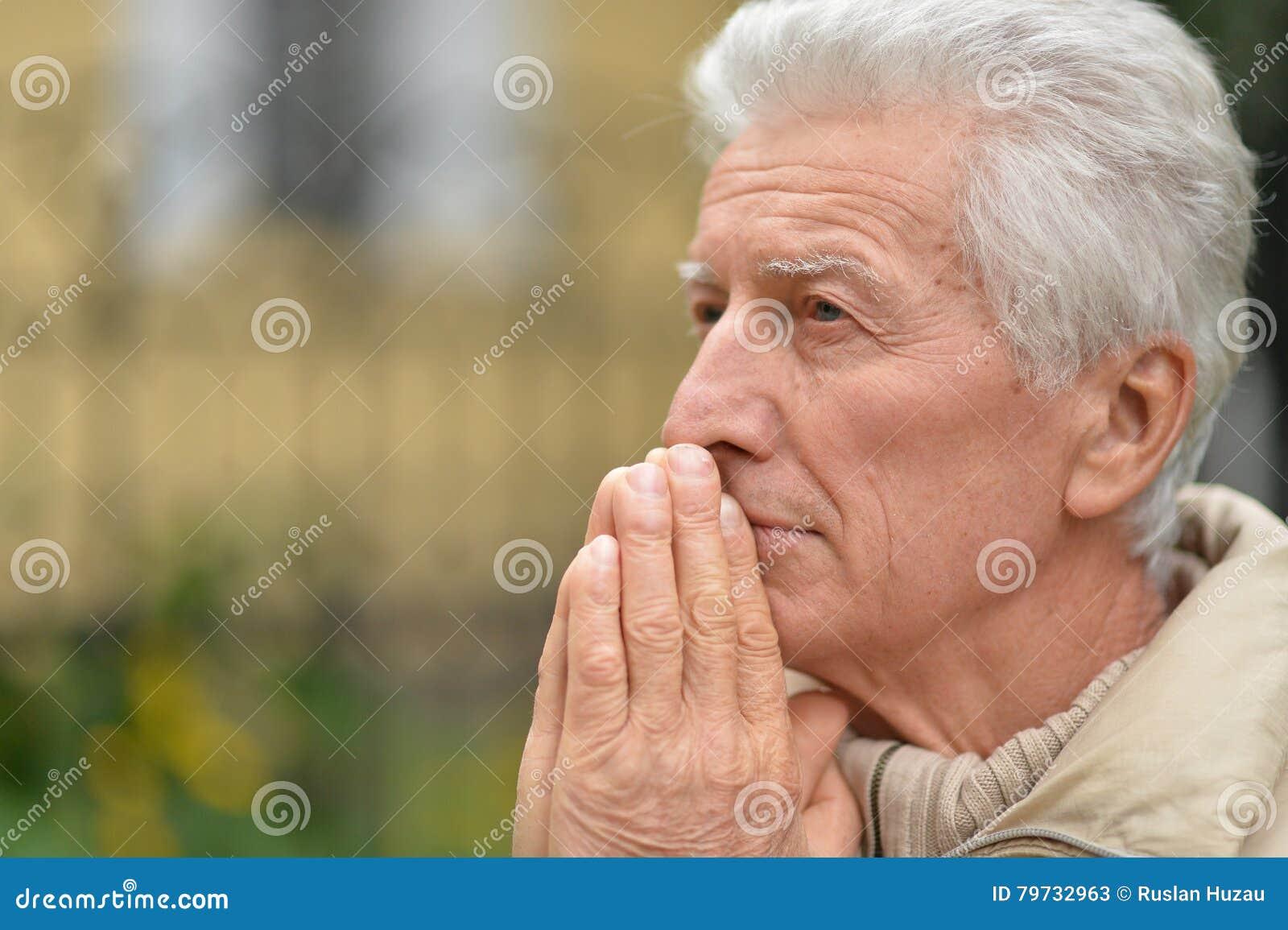 Hombre mayor triste al aire libre