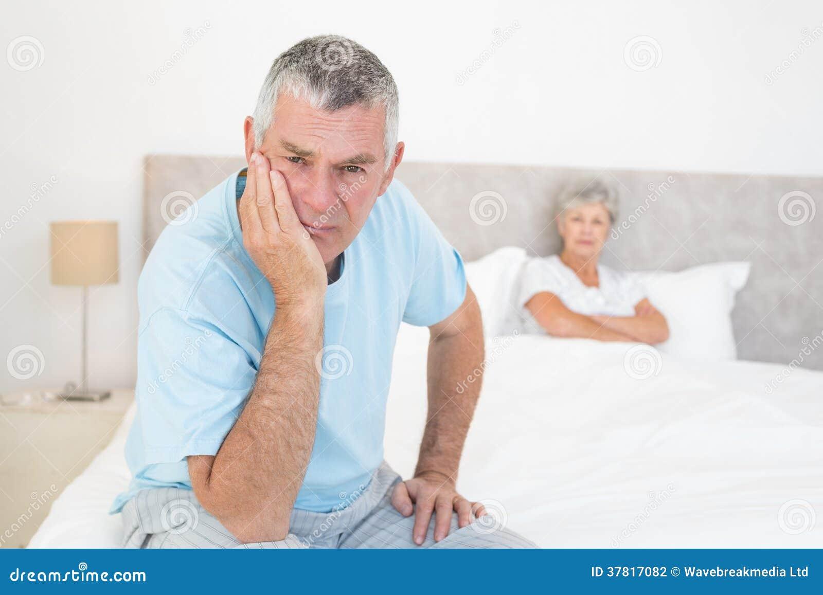 Hombre mayor triste con la mujer en cama