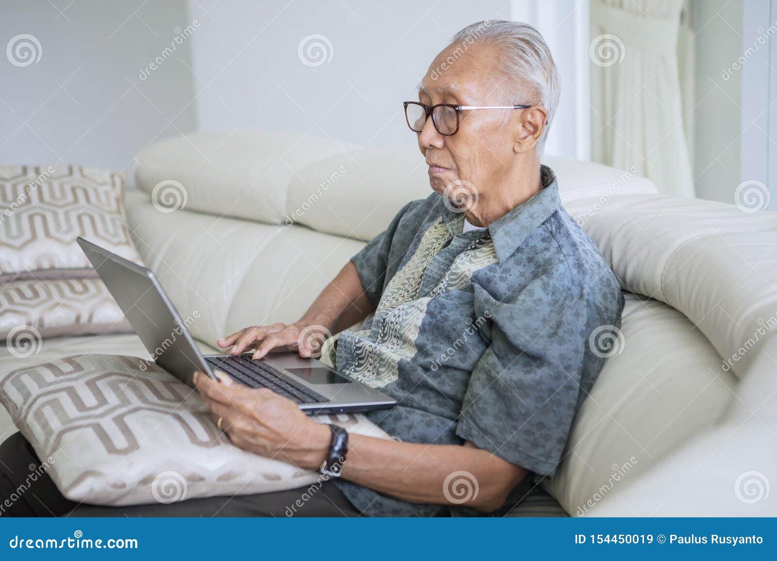 Hombre mayor usando un ordenador portátil en casa