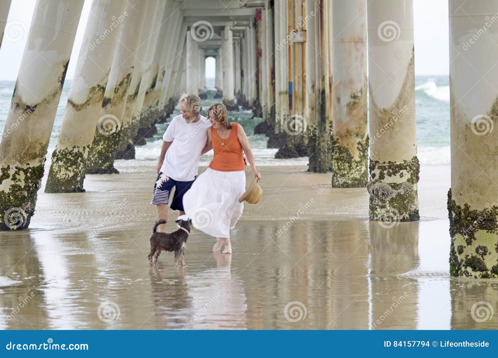 Hombre mayor y mujer que disfrutan de un día de fiesta relajante romántico en la playa con el perro casero