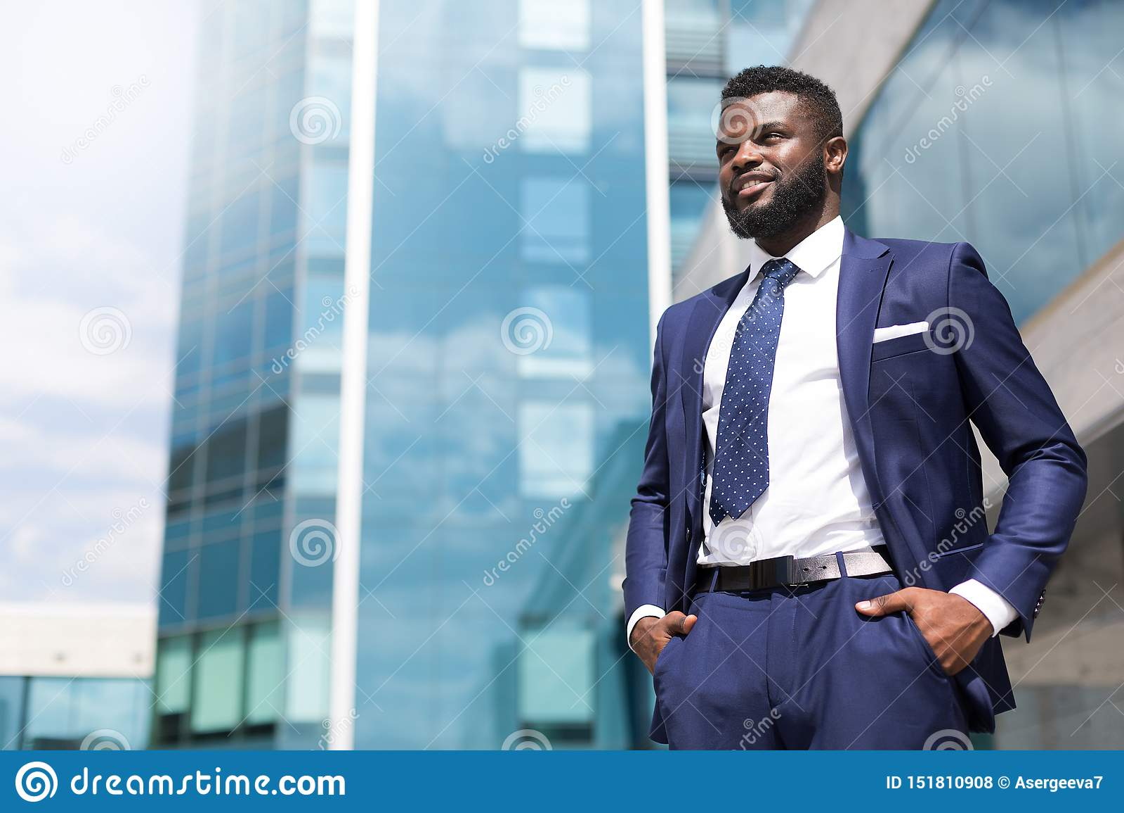 Hombre millenial africano en el traje que se coloca cerca del edificio de oficinas llenado de gratitud con el espacio de la copia